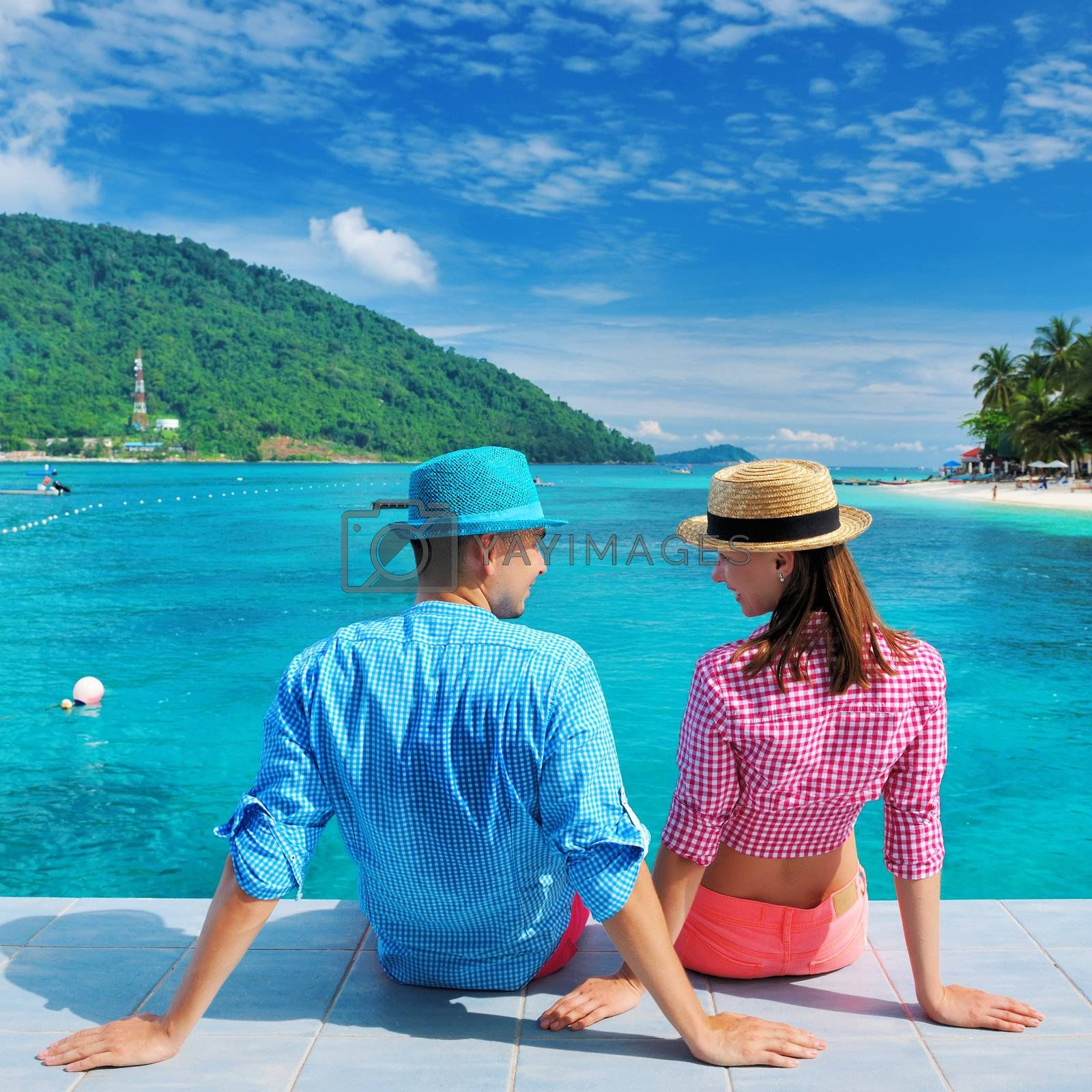 Couple at beach jetty wearing hat