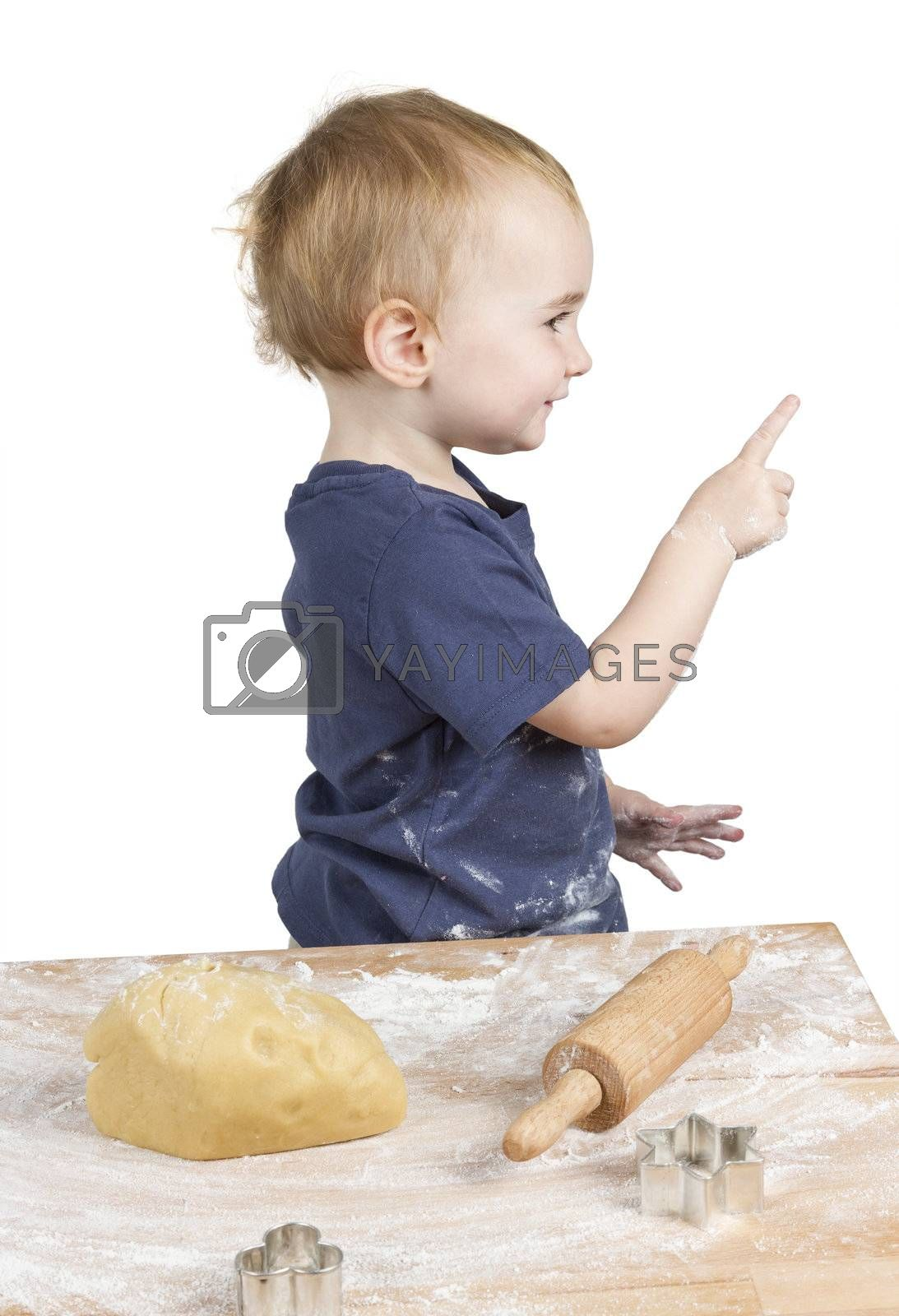 young child making cookies pointing at side