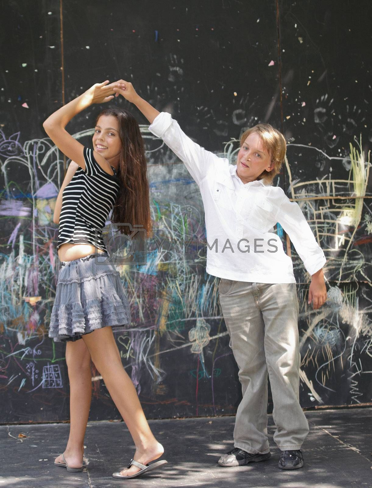 Portrait of a girl dancing near a wall with graffiti.