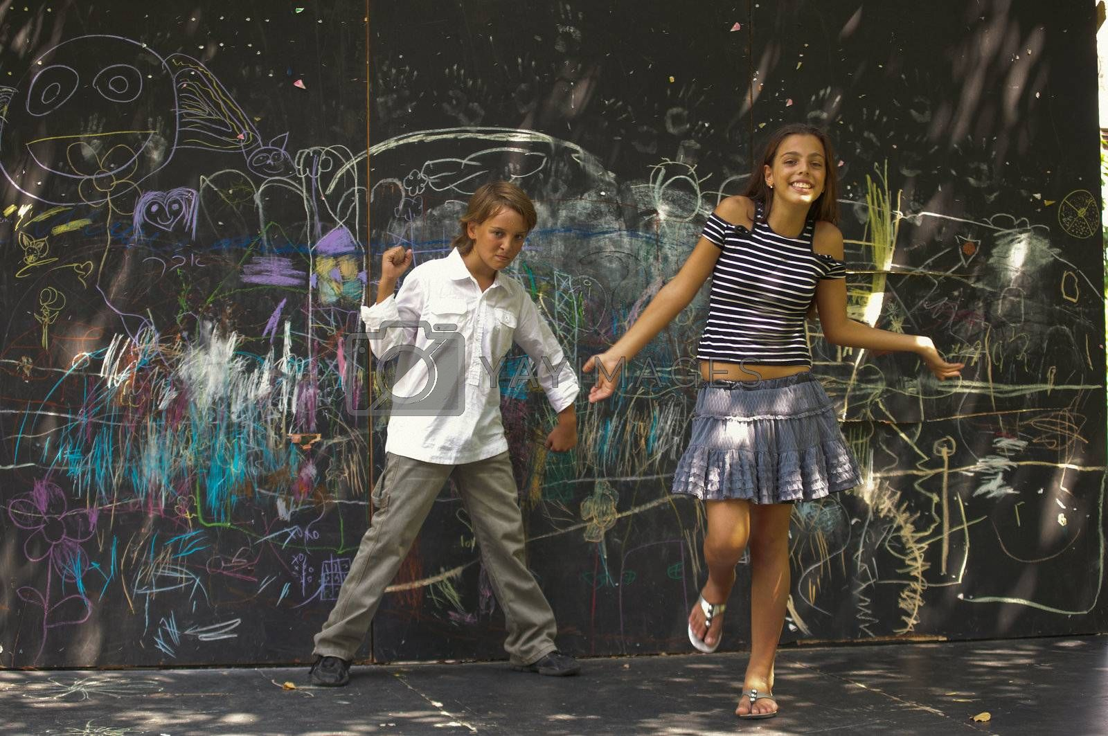 Portrait of  dancing boys and girls near a wall with graffiti.