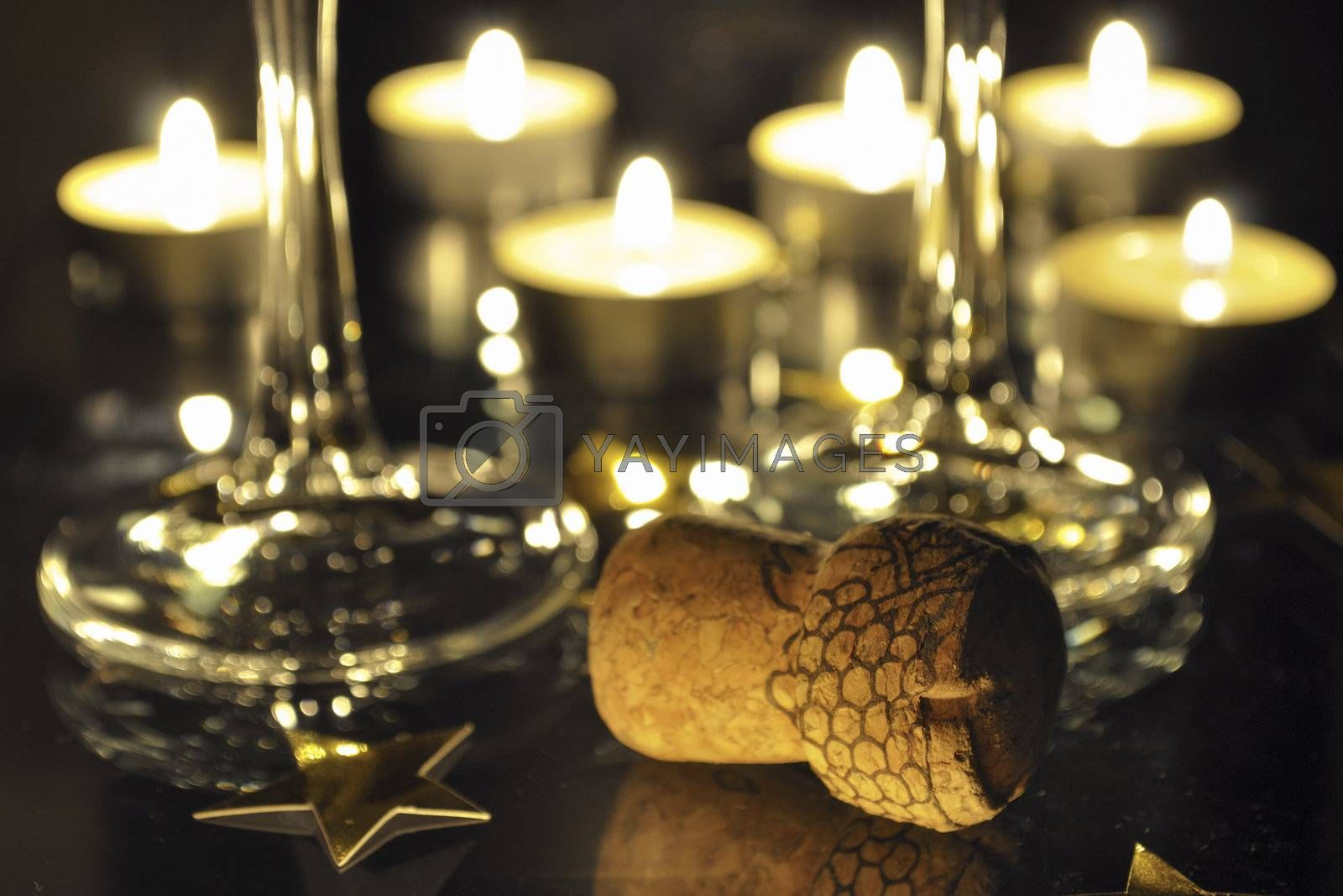 holiday still-life with Champagne cork , two glasses and many candles behind; focus on foreground cork