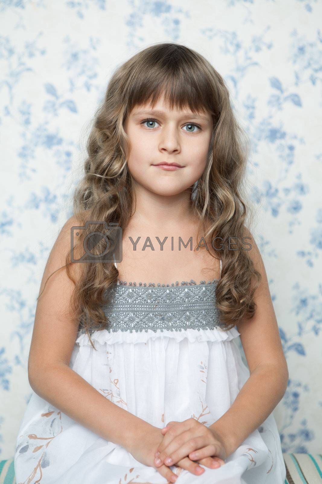 Portrait of sincere cheerful tender young blond girl child with grey eyes and wavy long hair in sitting posture looking at camera