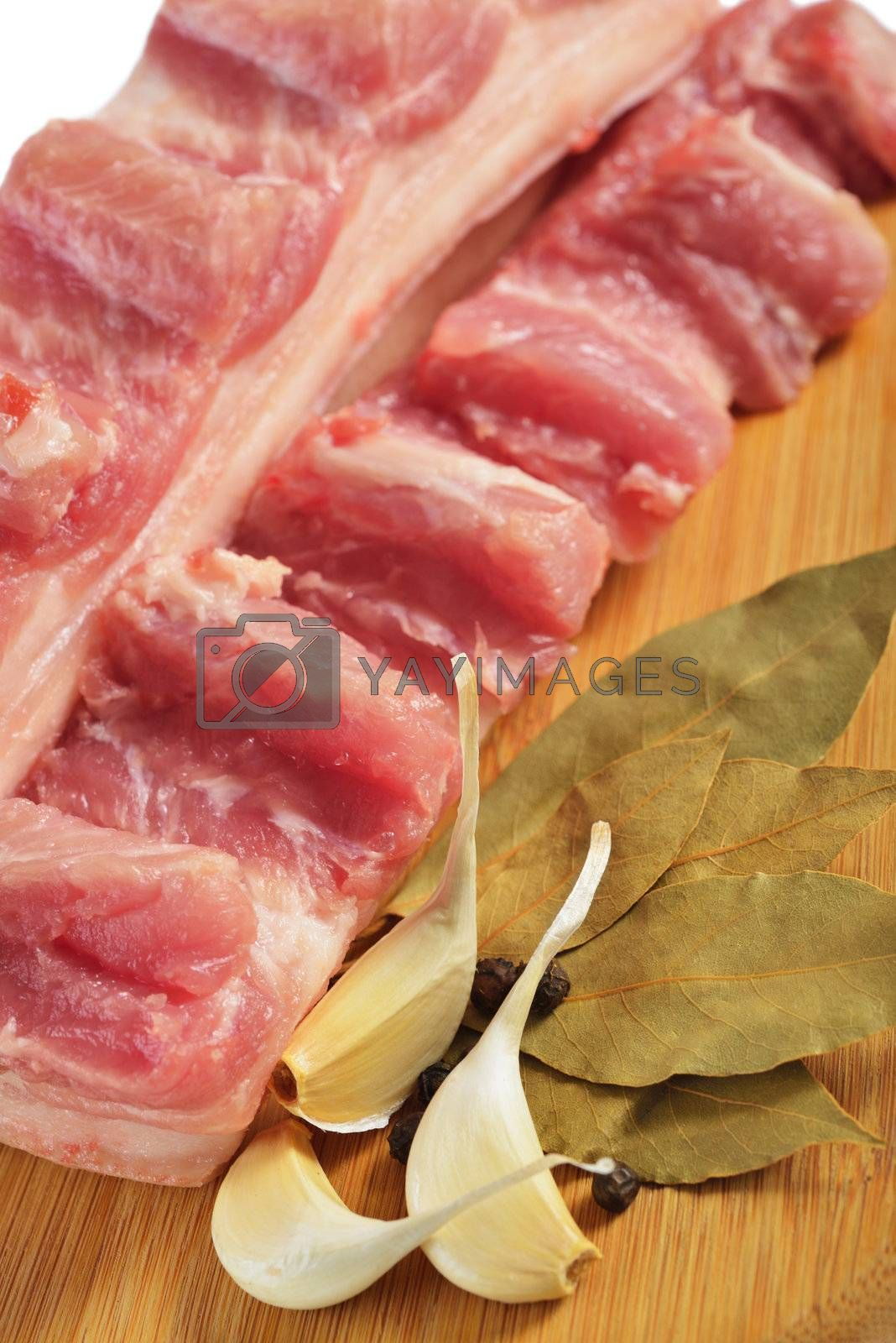 Raw bacon with ribs on a wooden cutting board.