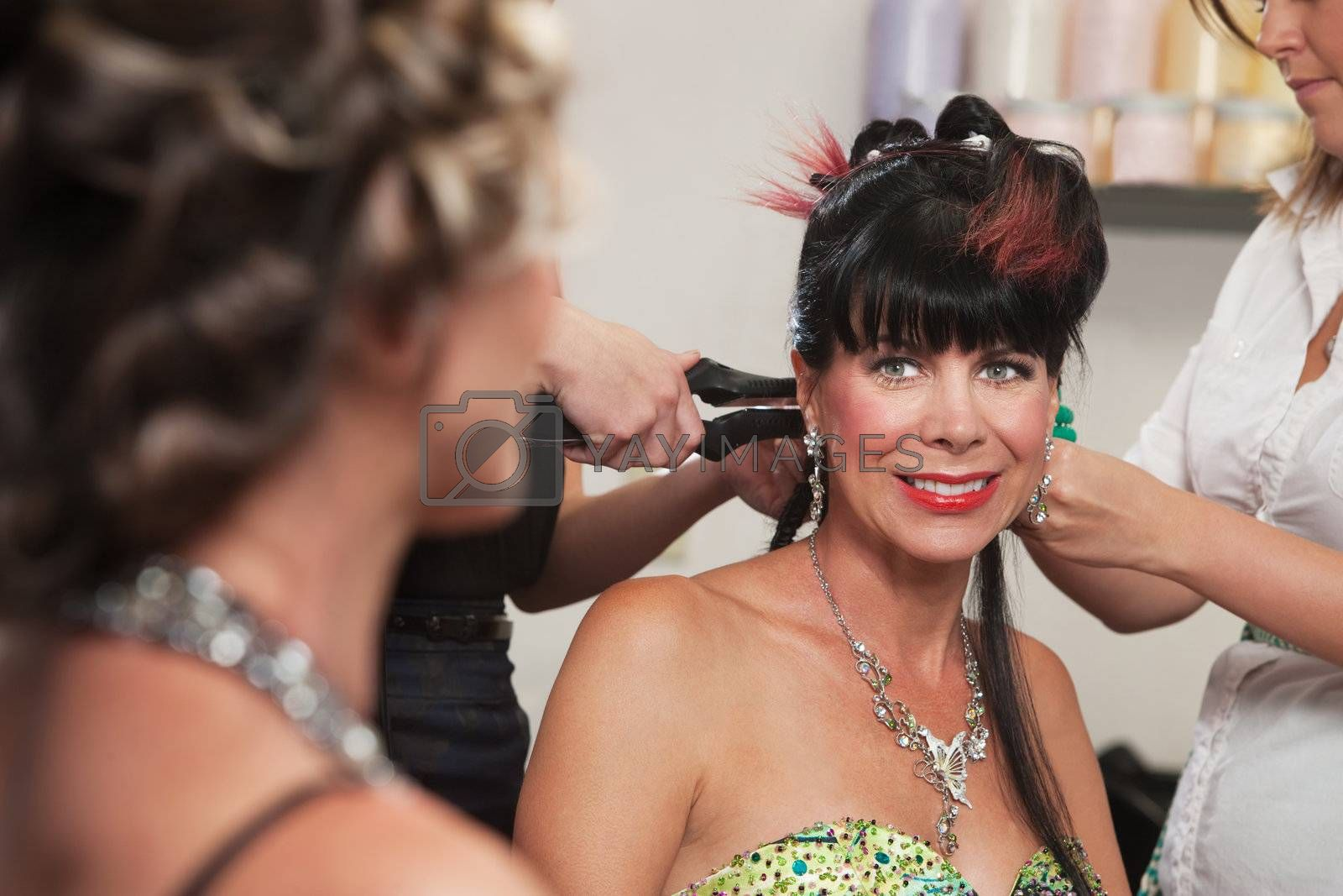 Smiling woman looking at lady with hair stylists working