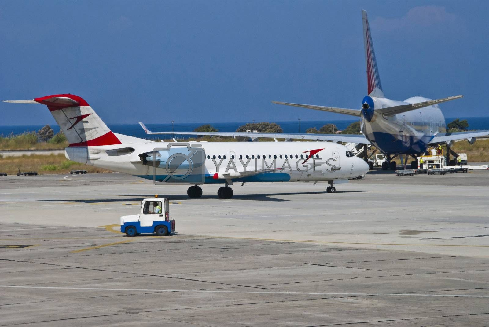 Fokker 70 of Austrian Arrows (Tyrolean Airways) parked at Rhodes airport, picture are shot from the departure hall at Rhodes airport.
