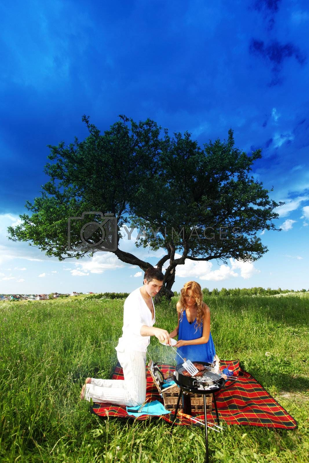 man and woman on picnic in green grass