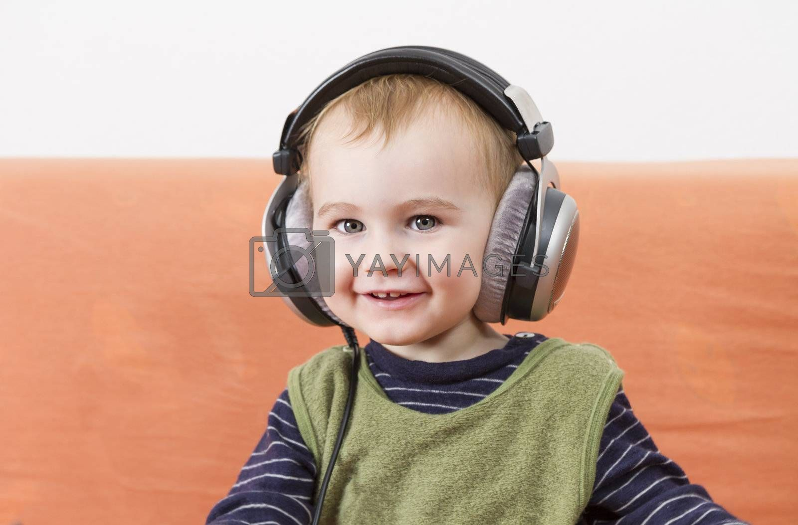 Royalty free image of young child on couch with headphone by gewoldi