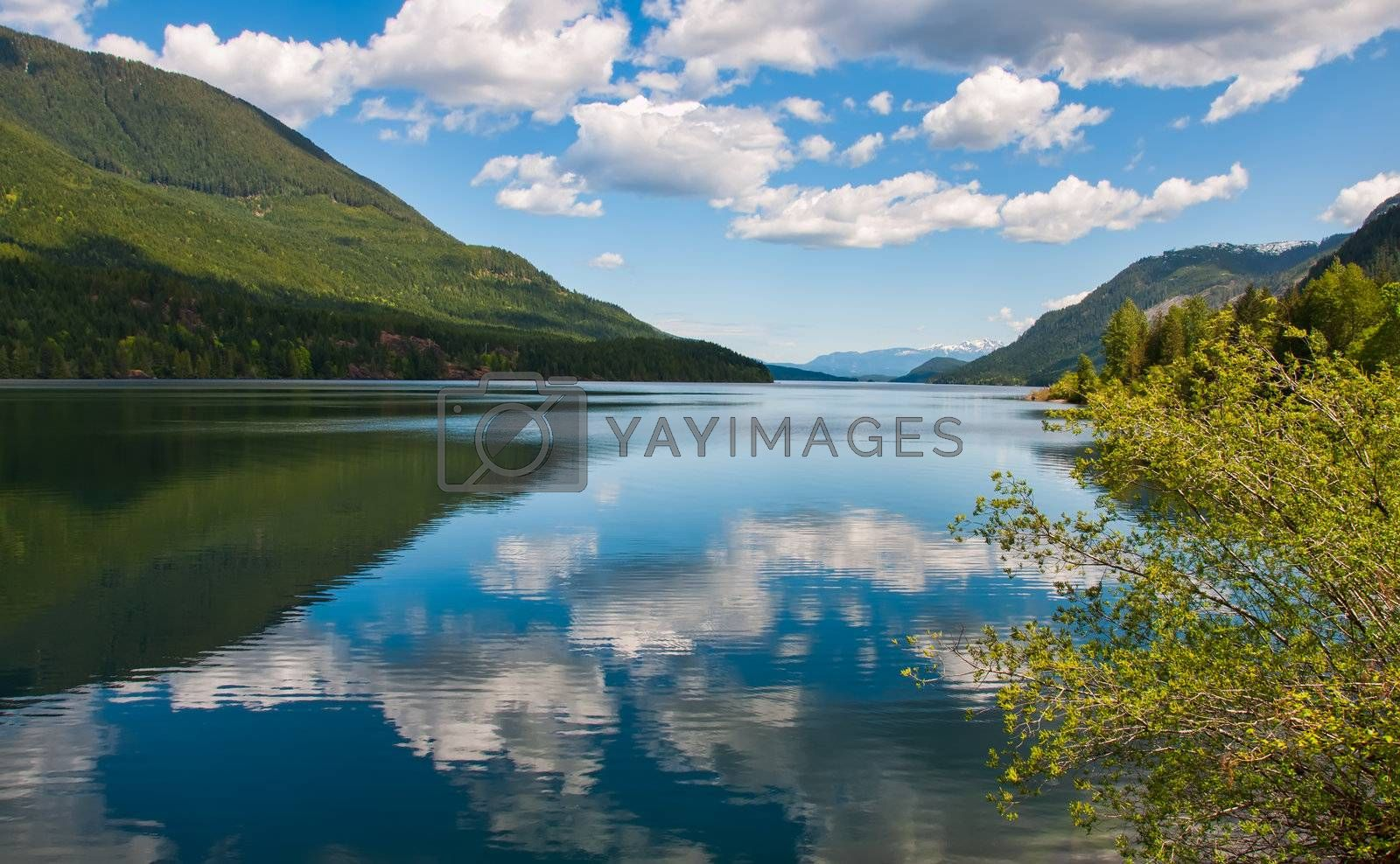Fluffy clouds reflected in a tranquil lake with mountains in distance