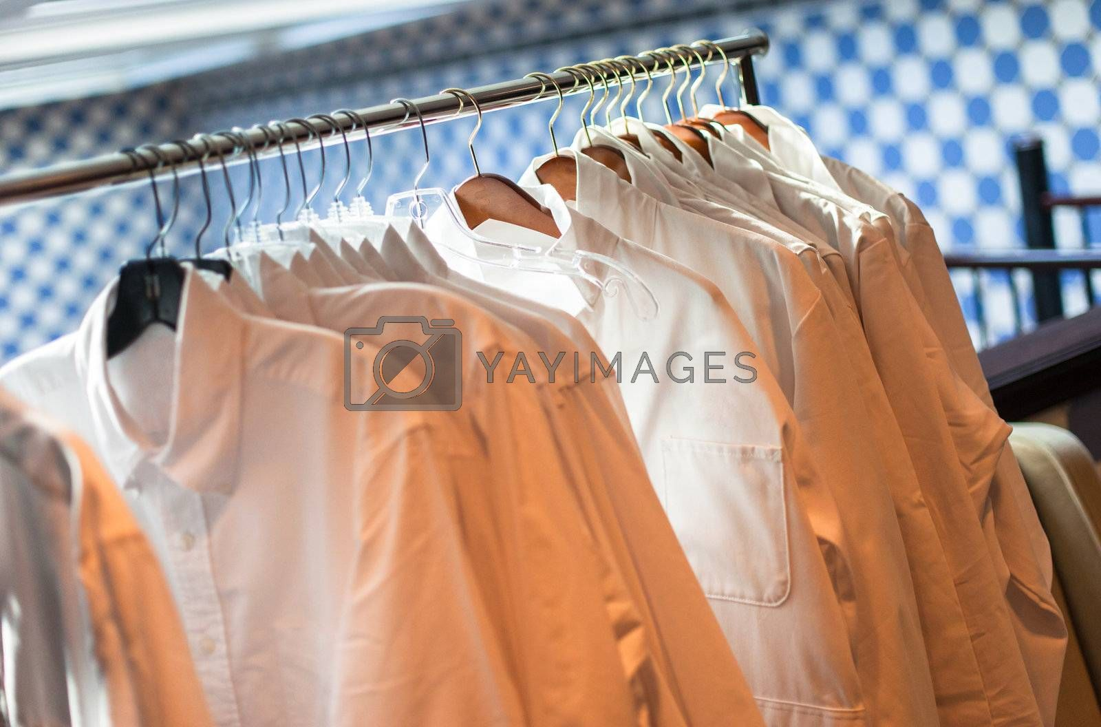 White men's shirts hanging on a rack indoors