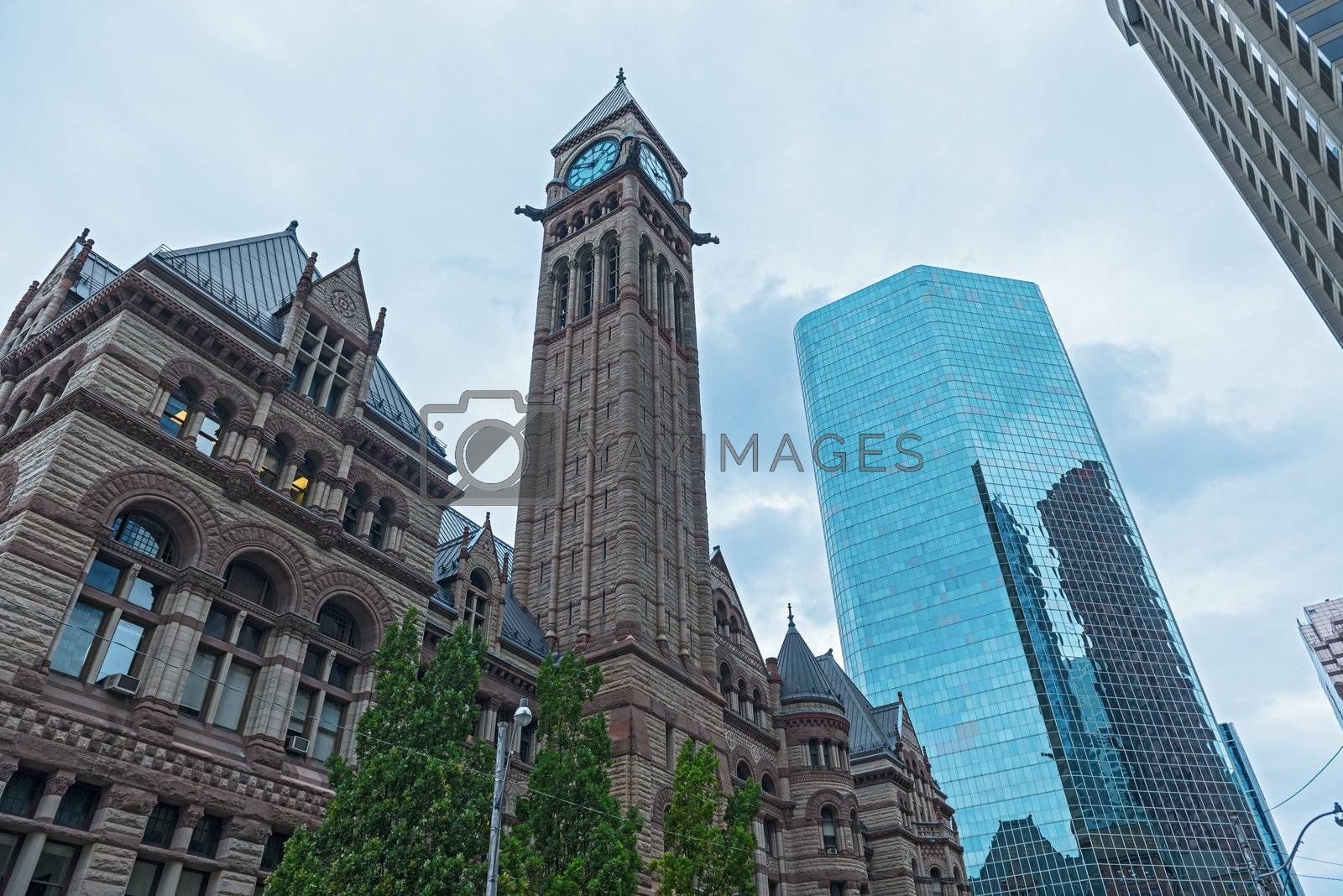 A view of the Old City Hall in Toronto with modern office buildings around it under blue skies.