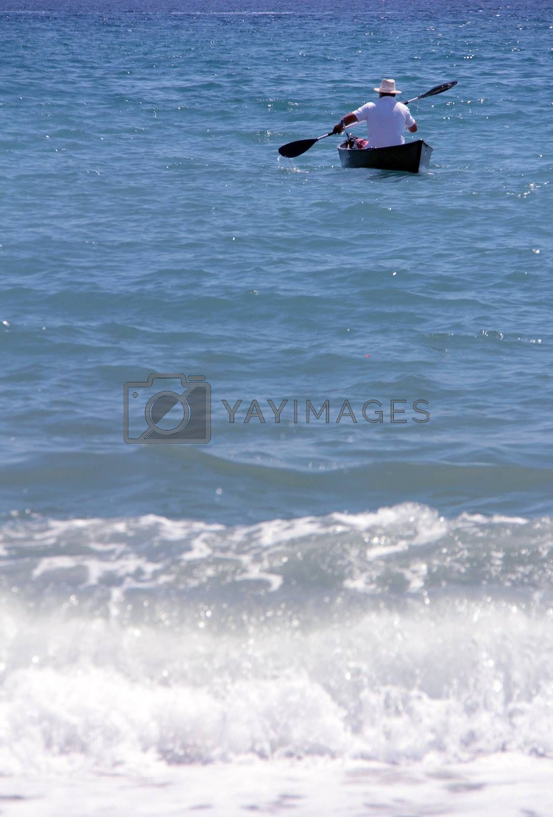 lonely man with rowing boat at the seaside