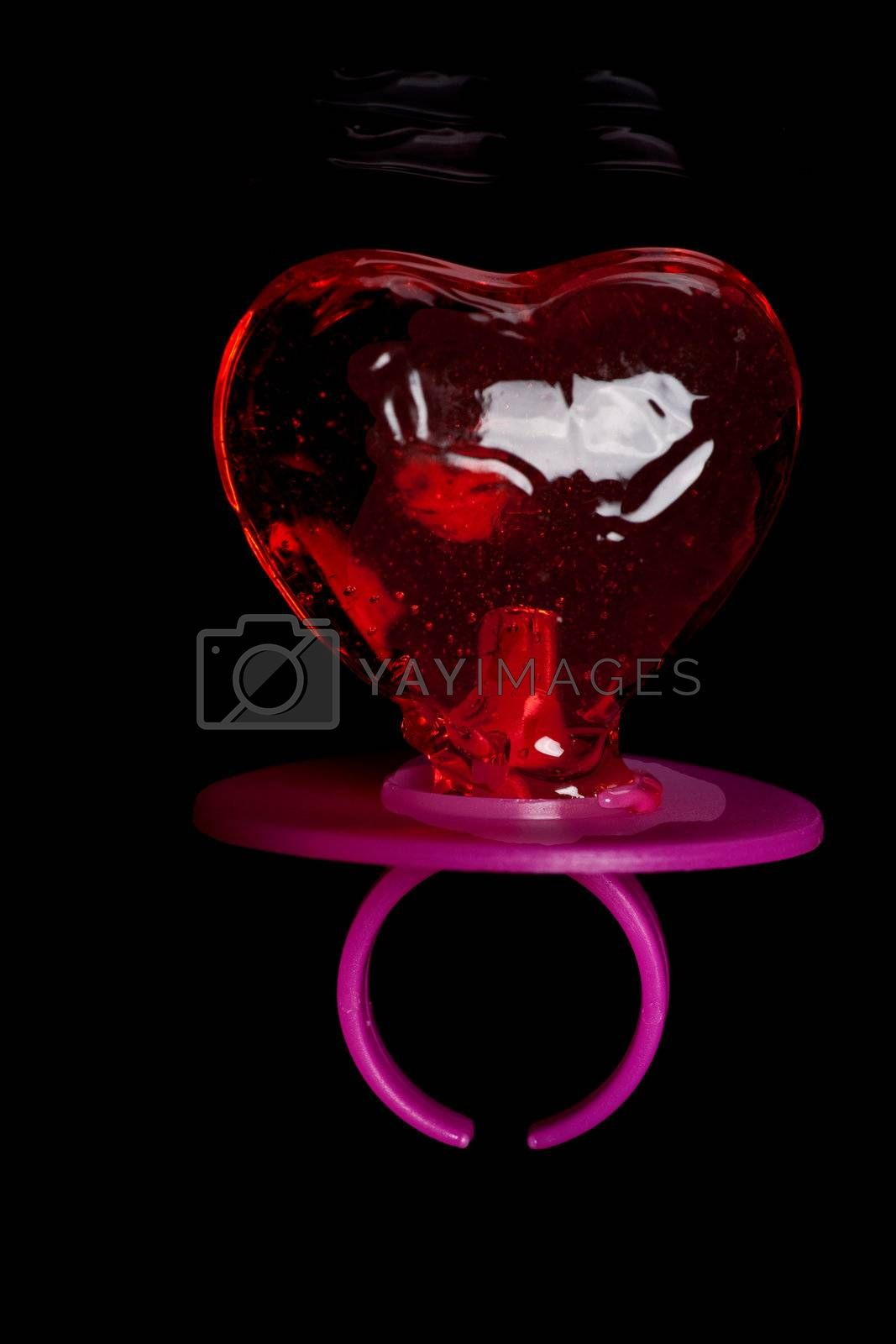 Baby teat in heart shape on black background