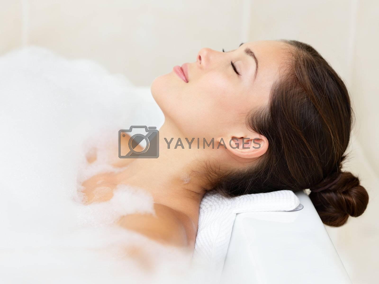 Bath woman relaxing bathing in bathtub with bath foam. Beautiful young mixed race Asian Caucasian female model in bathroom.