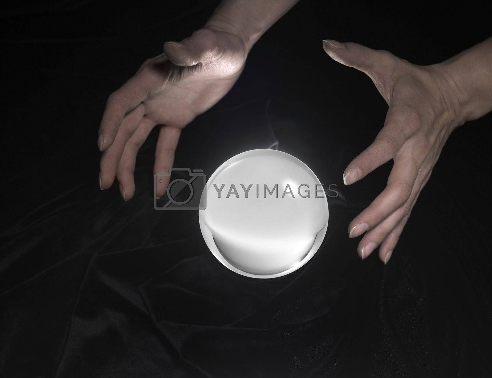 high angle shot of a glowing crystal ball surrounded by black crinkly fabrics and two hands around
