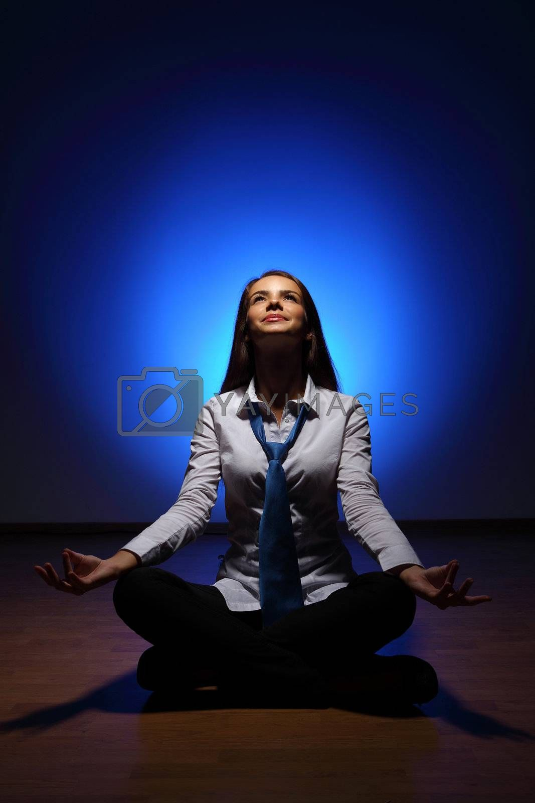 Young business woman sitting in asana lotus and meditating