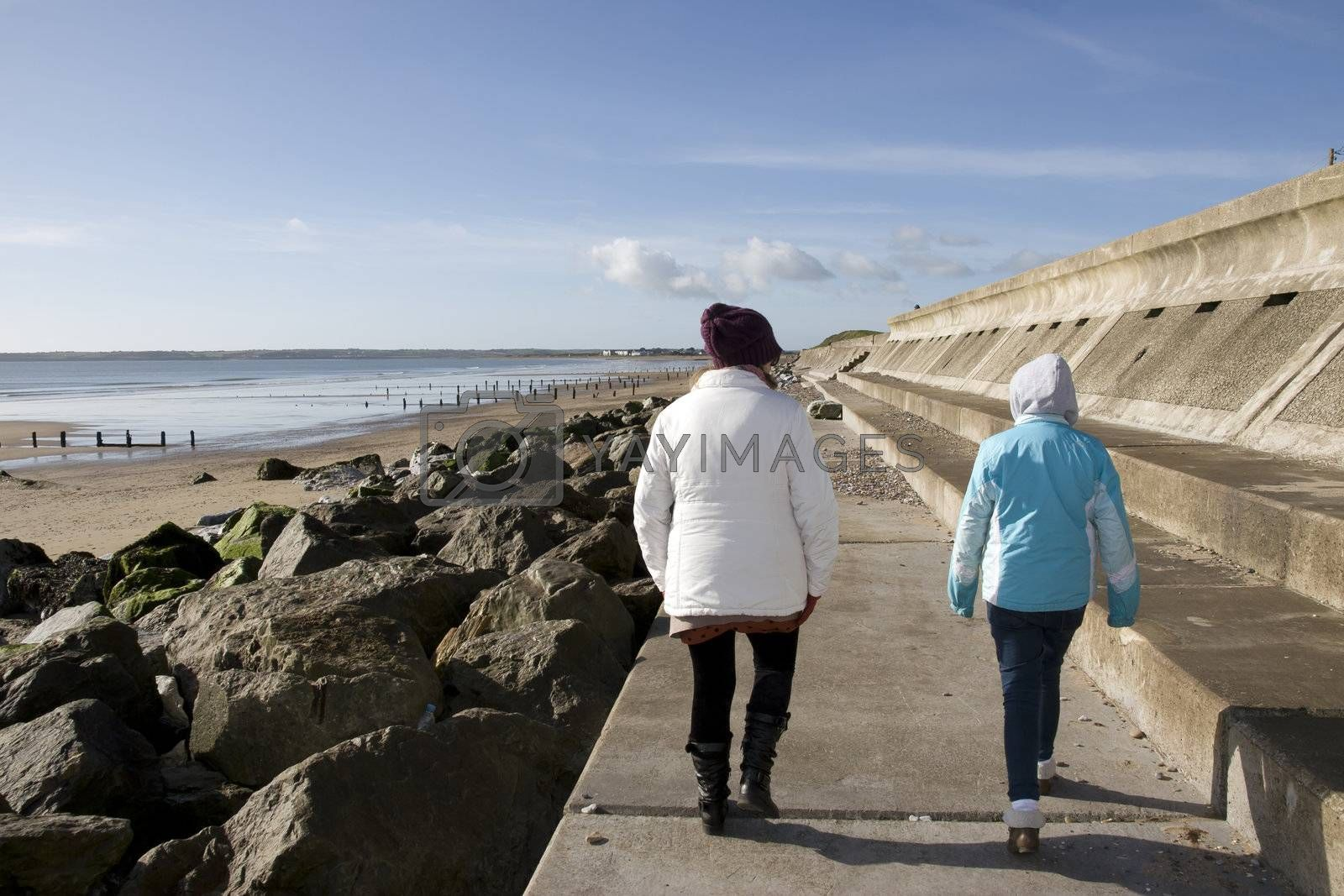mother and daughter strolling along the beach promenade in Youghal county Cork Ireland
