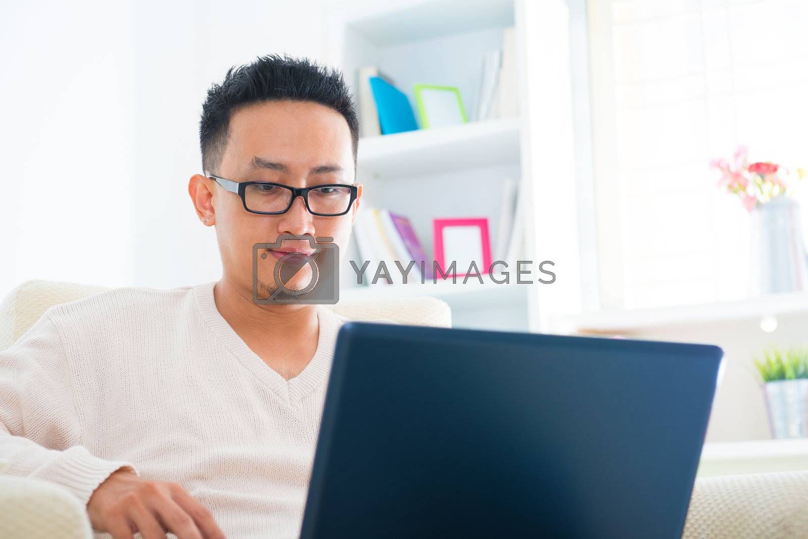 Southeast Asian male using notebook sitting on sofa at home, living lifestyle