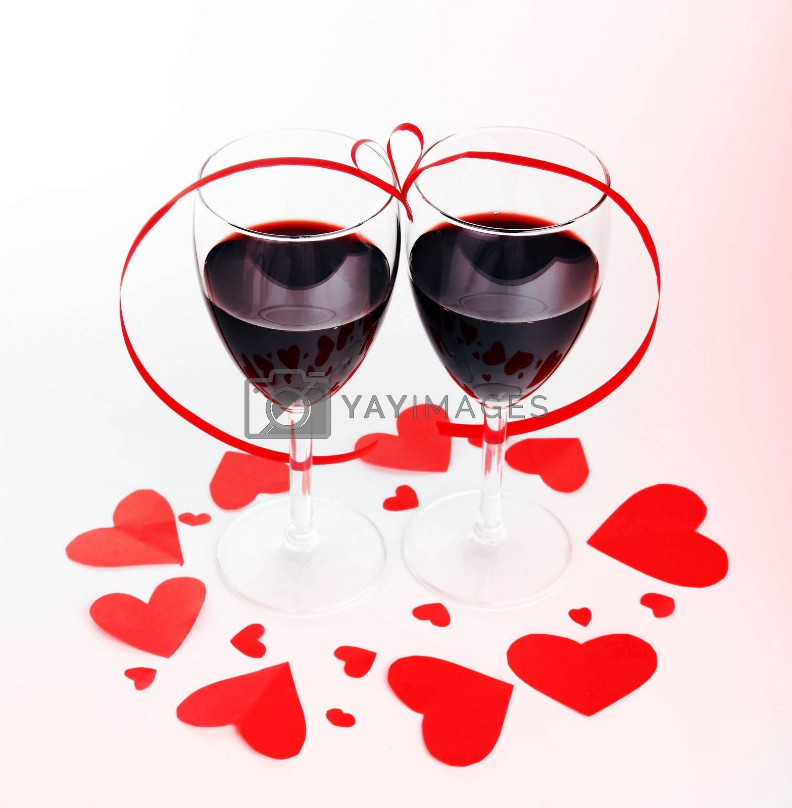 Romantic holiday drink, celebration of valentine's day, red wine with hearts ornament & ribbon decoration, isolated on white background