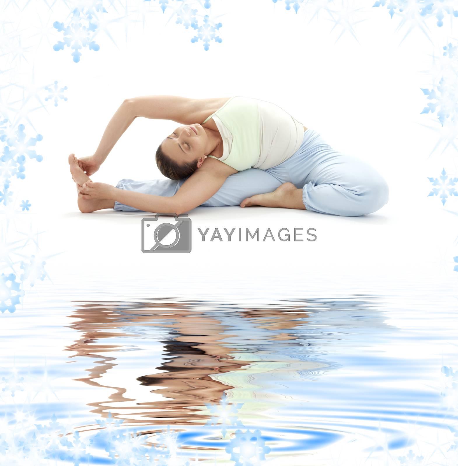lovely girl practicing ashtanga yoga on white sand