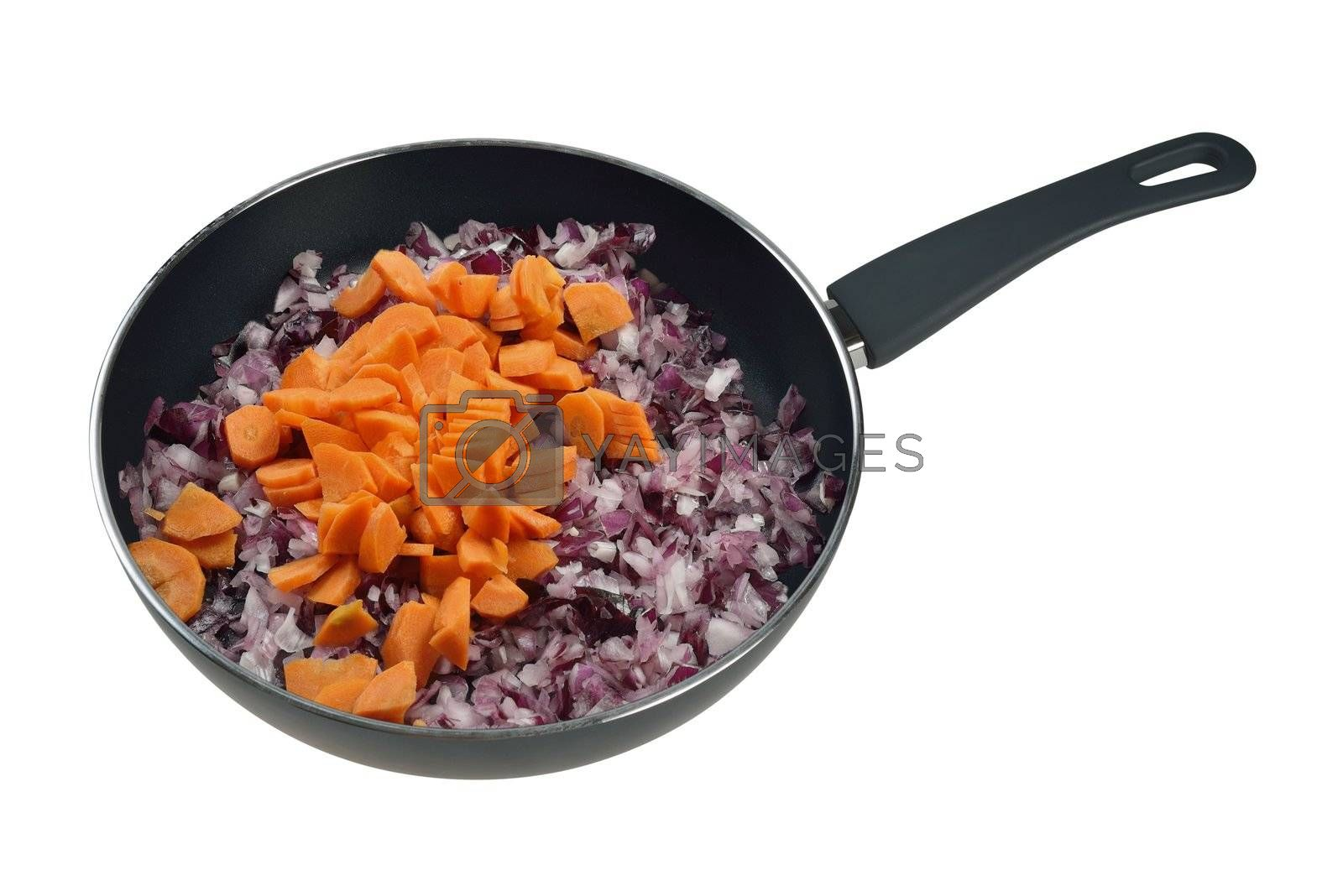 Onions and carrots in a frying pan. Isolated on white.