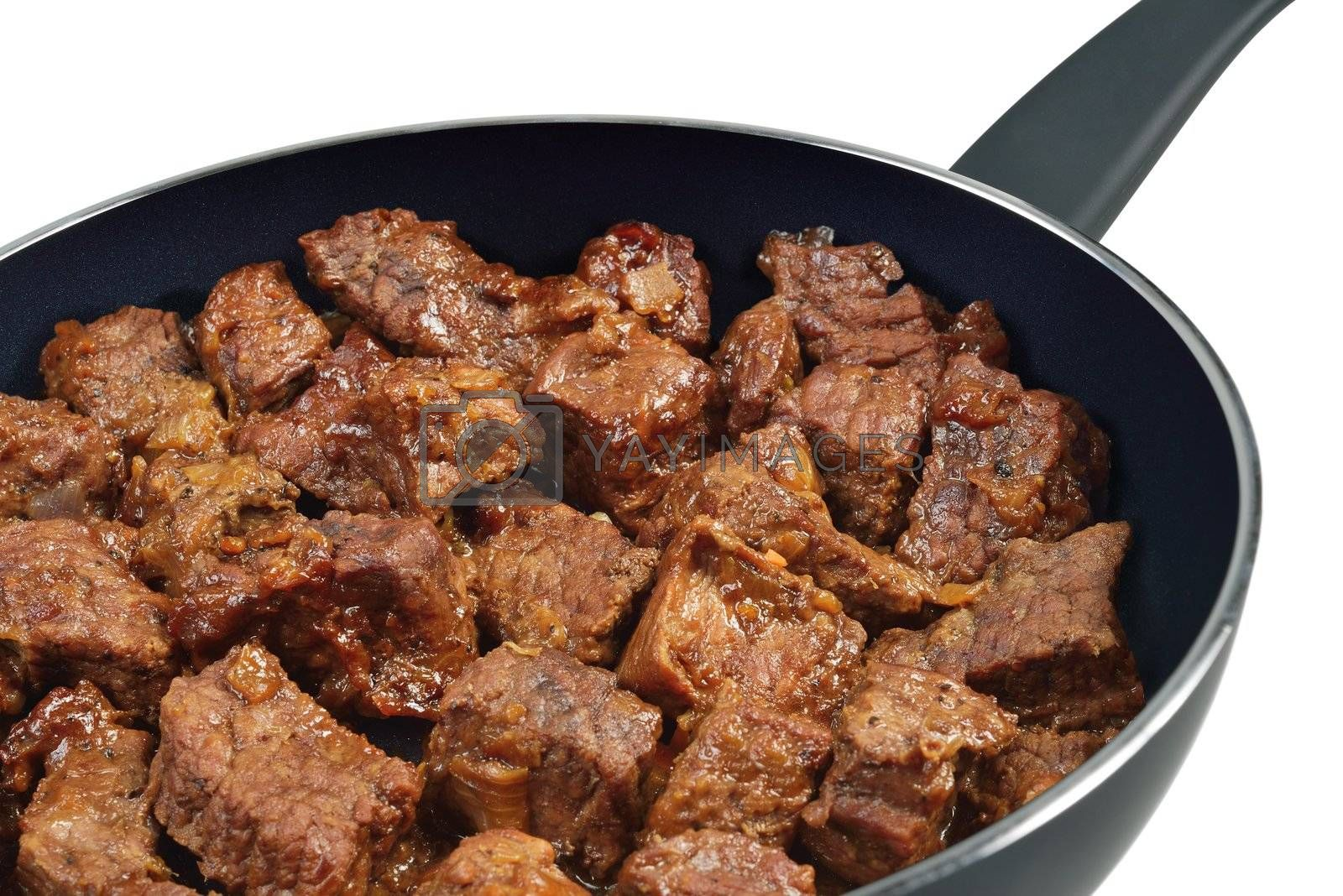 Beef stew in a frying pan. Isolated on white.