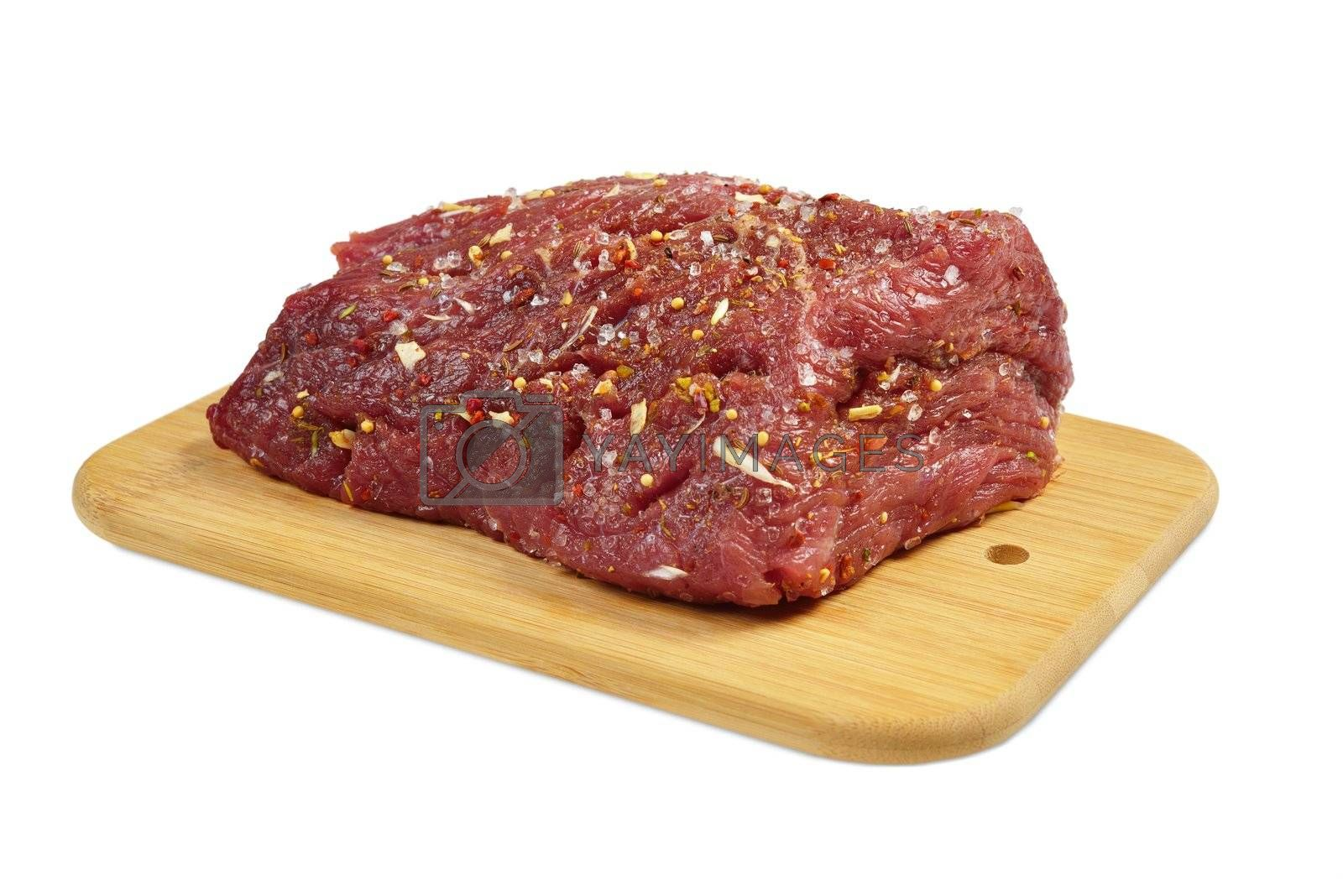 Beef on a wooden board with spices. Isolated on white