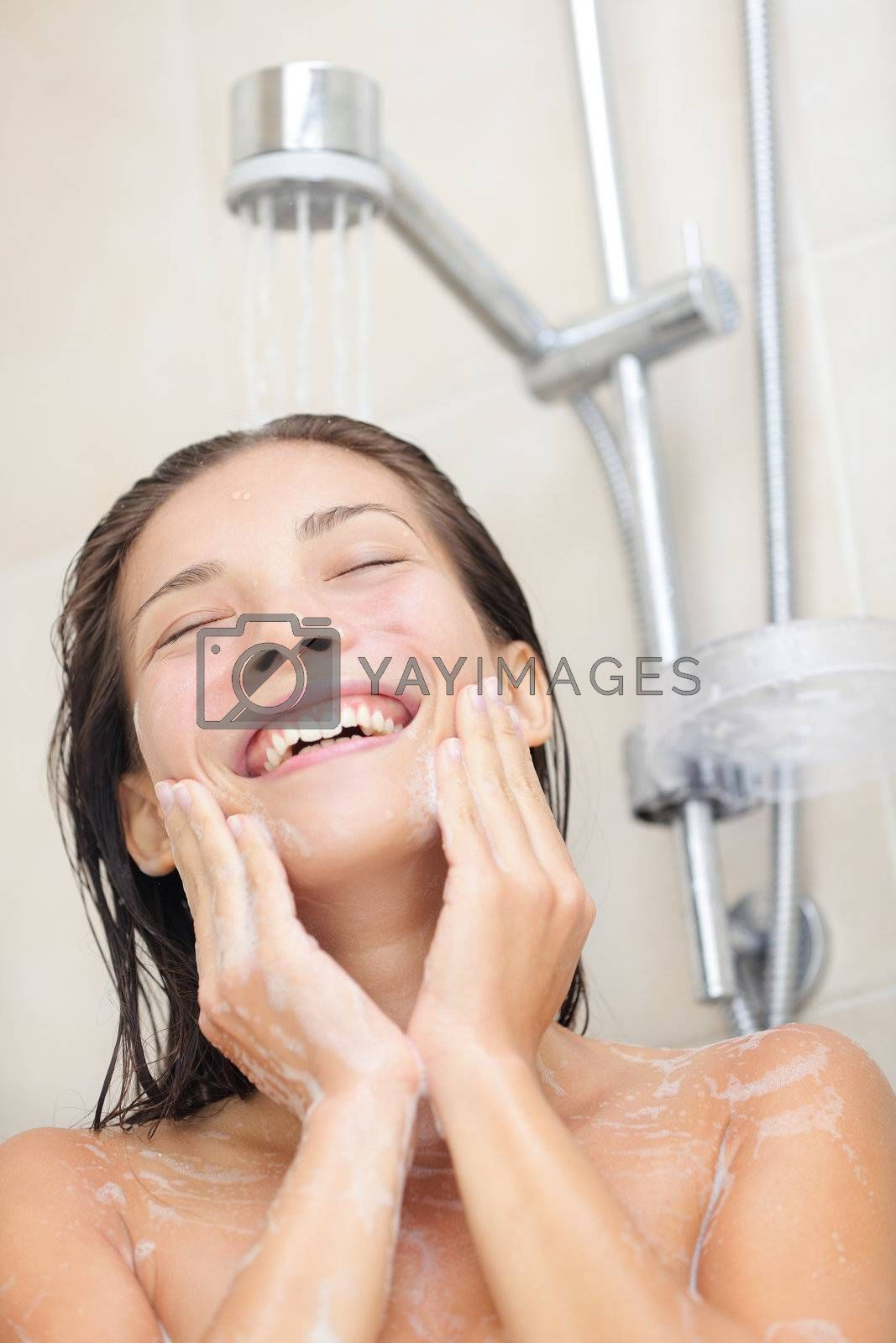Woman washing face in shower. Showering asian woman enjoying water splashing on face while cleaning face. Portrait of multiracial Asian / Caucasian girl smiling happy. Model in her 20s.