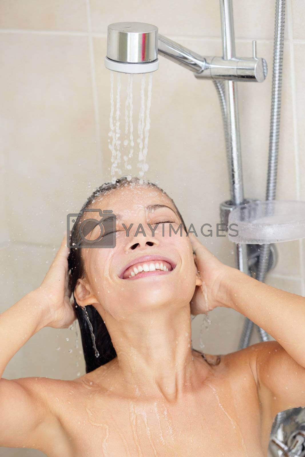 Woman washing hair enjoying showering smiling happy with face under running water. Beautiful mixed race Caucasian / Asian Chinese model in her twenties.