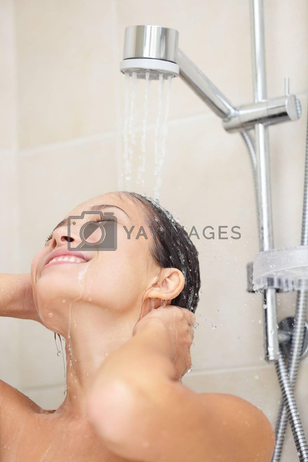 Shower woman showering under running water in bathroom. Smiling happy portrait of Asian woman in her twenties.