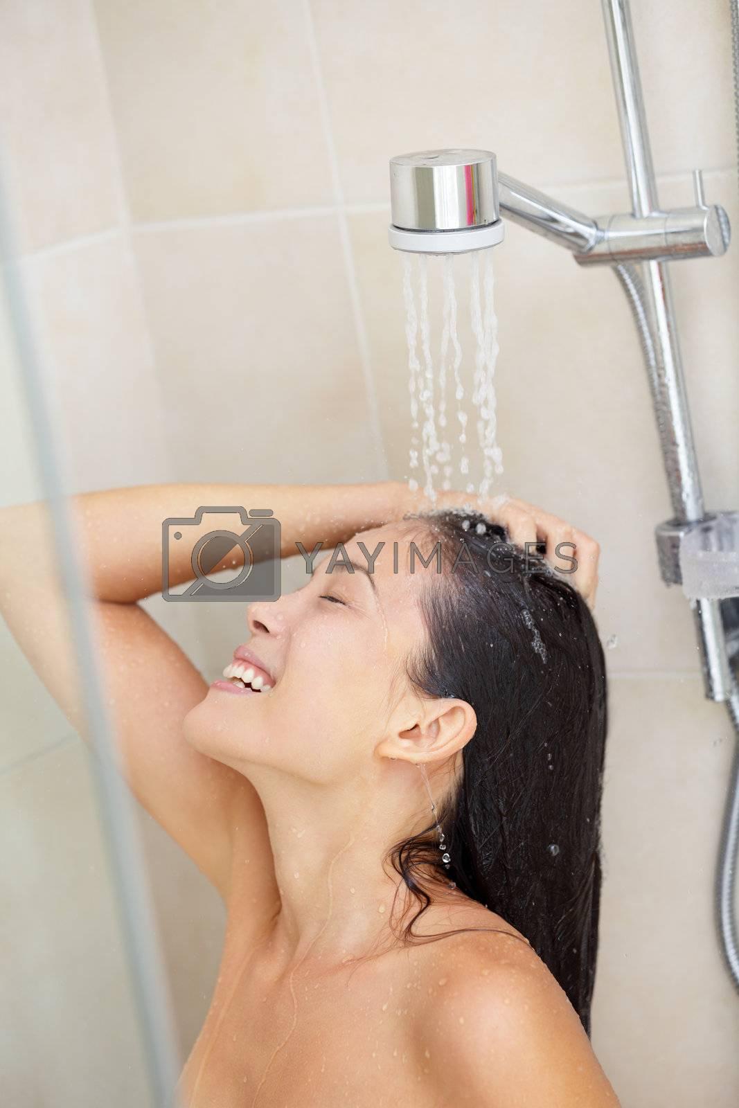 Washing hair. Shower woman washing hair enjoying showering under splashing water. Happy smiling pretty multiracial Asian / Caucasian female model at home in bathroom. Model in her 20s.