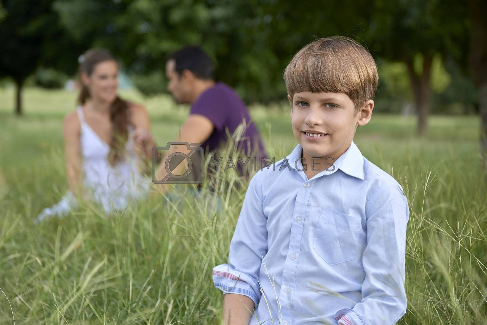 People and recreation, happy boy with mother and father in background. Front view