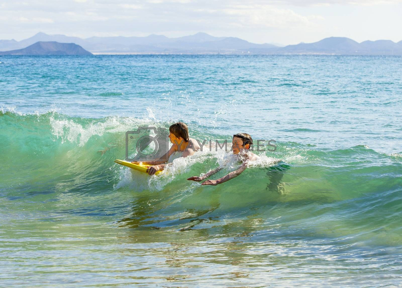 boys have fun riding in the waves