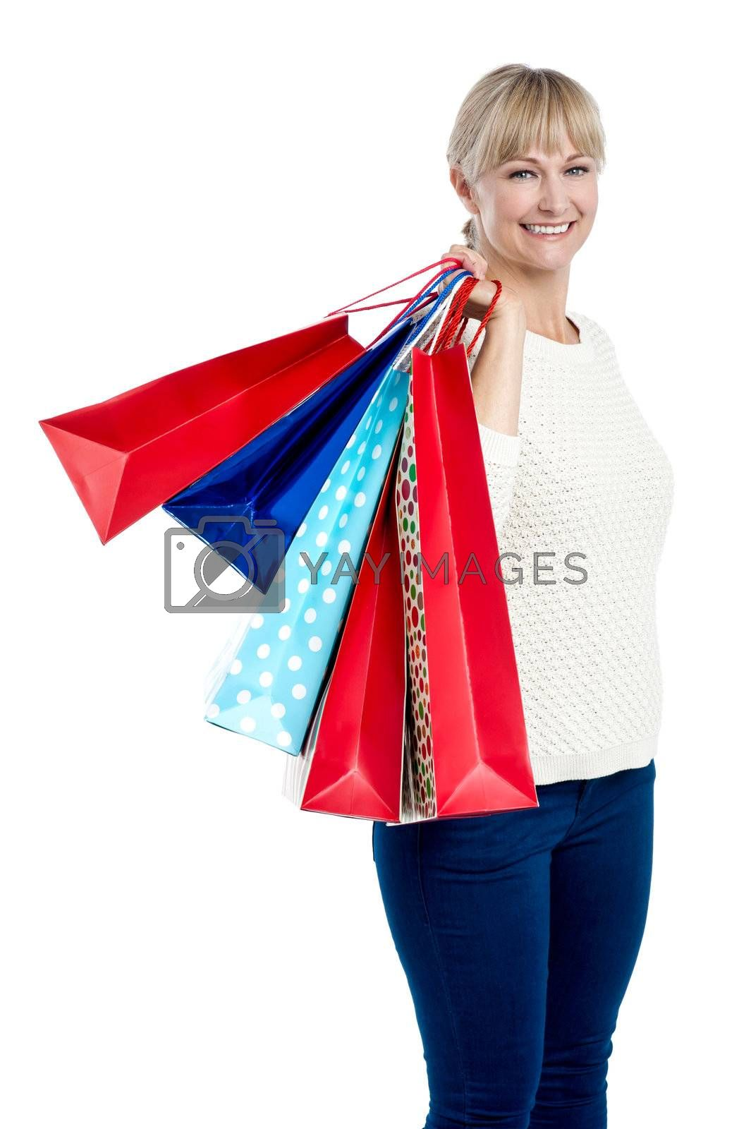 Stylish woman with colorful shopping bags slung over her shoulder.