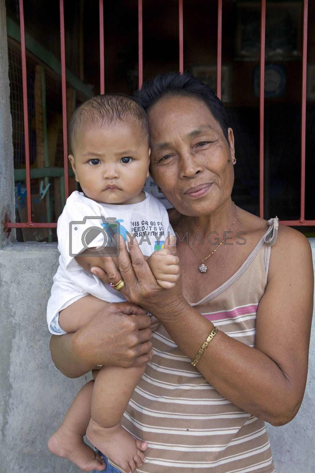 May 2012 - Cadiz City, Negros Oriental, Philippines - Pride and love expressed on the face of a Filipino grandmother holding her baby boy grandchild. Family is most important of all in the Philippines.