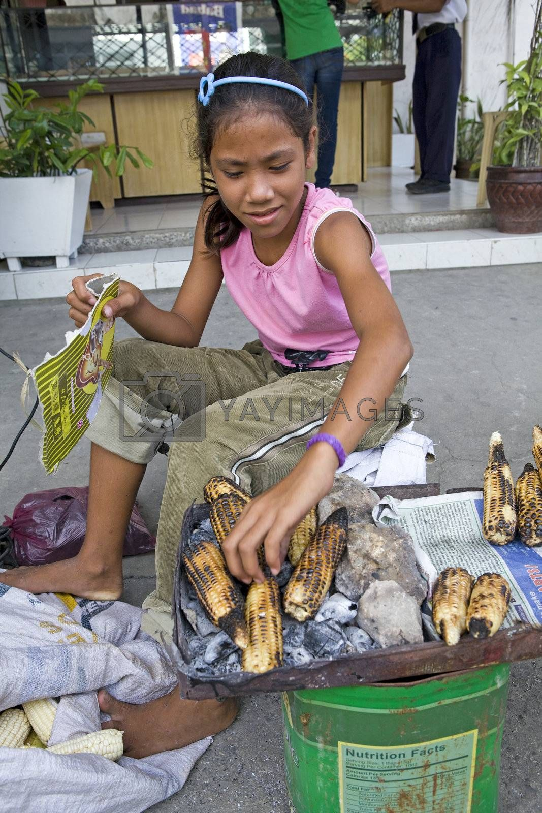 May 2012 - Bogo City, Cebu Island, Philippines - A beautiful twelve year old girl helps her mother earn money by roasting ears of corn over a charcoal fire to sell on the side of the road in Bogo City, Philippines.