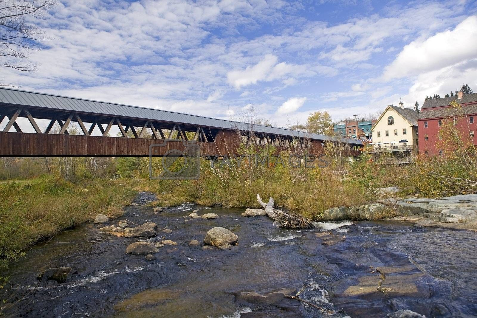 Autumn scenic of the restored wooden covered bridge over the Ammonoosuc River In Littleton, New Hampshire.