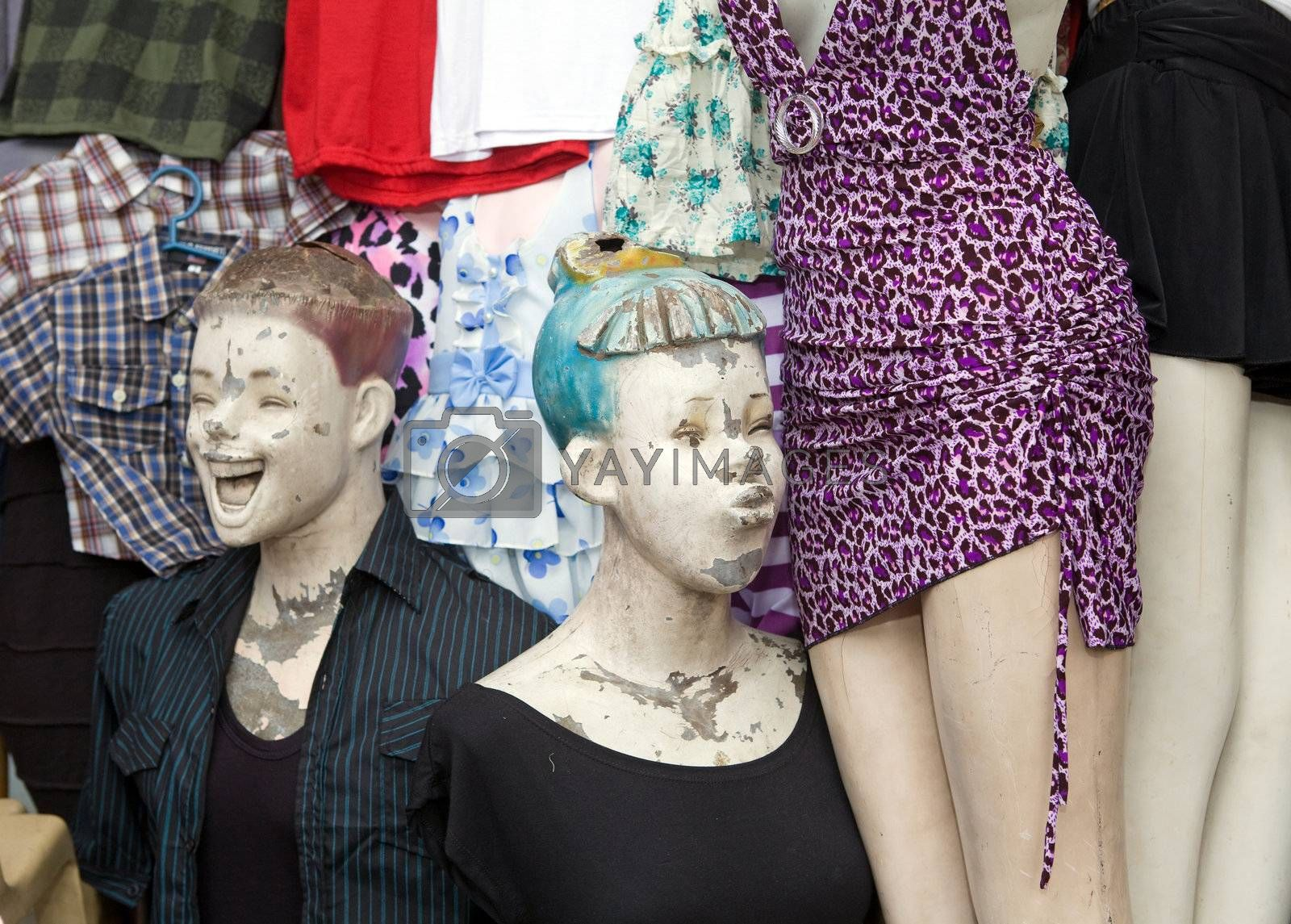 Two mannequin dummies outside a clothing store posed in a funny way. One is looking at the crotch of another dummy in a purple dress and the other is laughing.