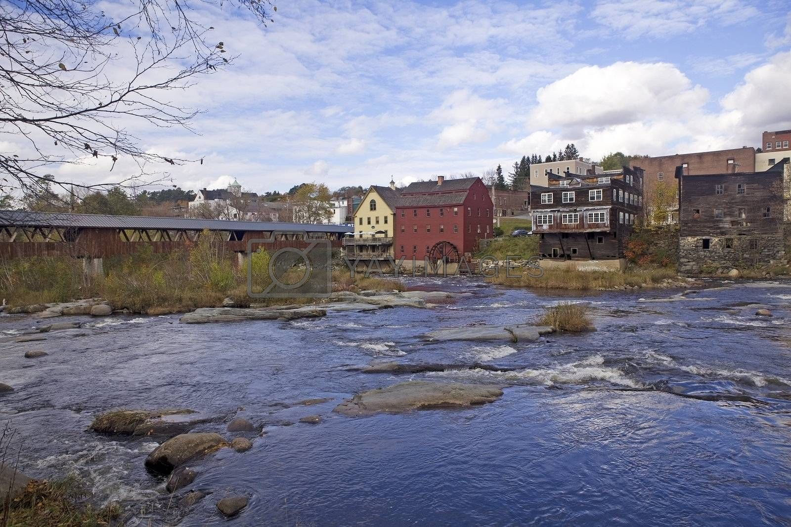 Ammonoosuc River flowing across rocks and under a covered bridge in Littleton, New Hampshire. An old grist mill and water wheel are near the bridge.