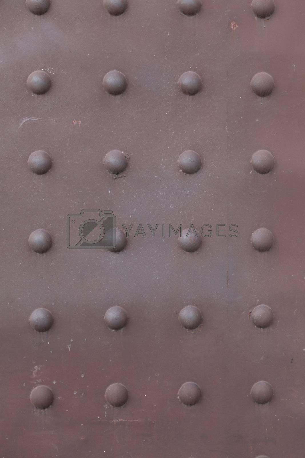 Background -  brown, rusty metal plate with vertical and horizontal rows of rivet heads.