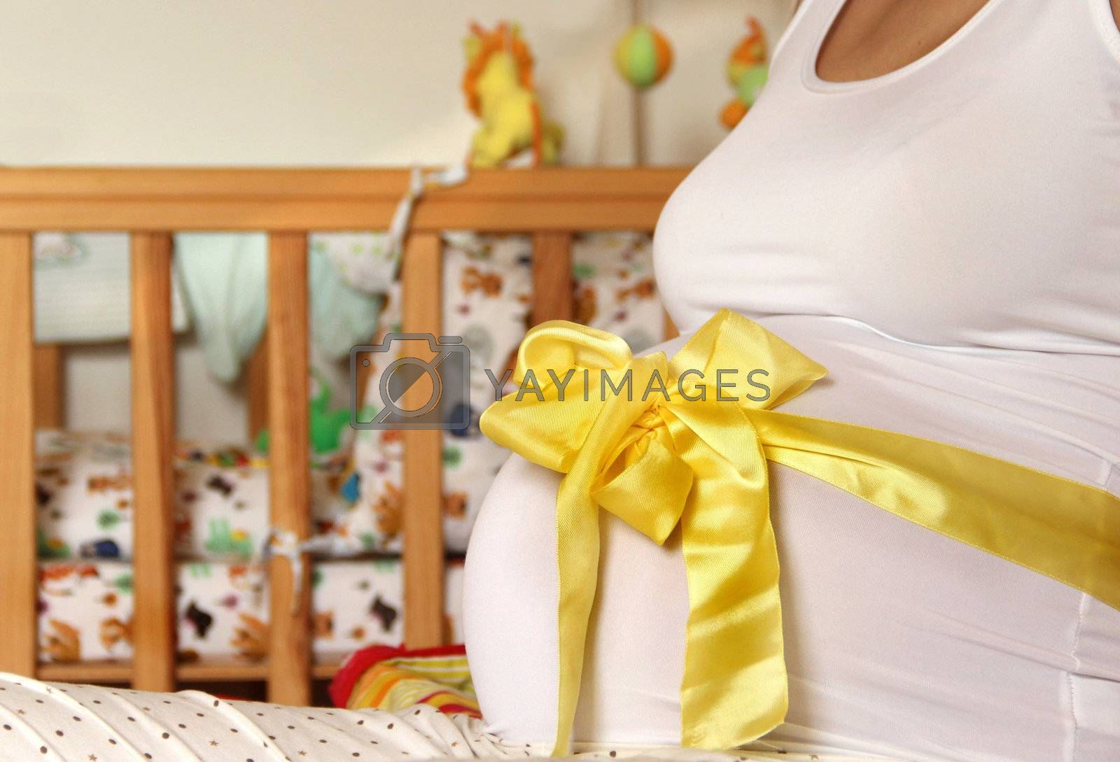 Pregnant woman tummy decorated with yellow ribbon and bow