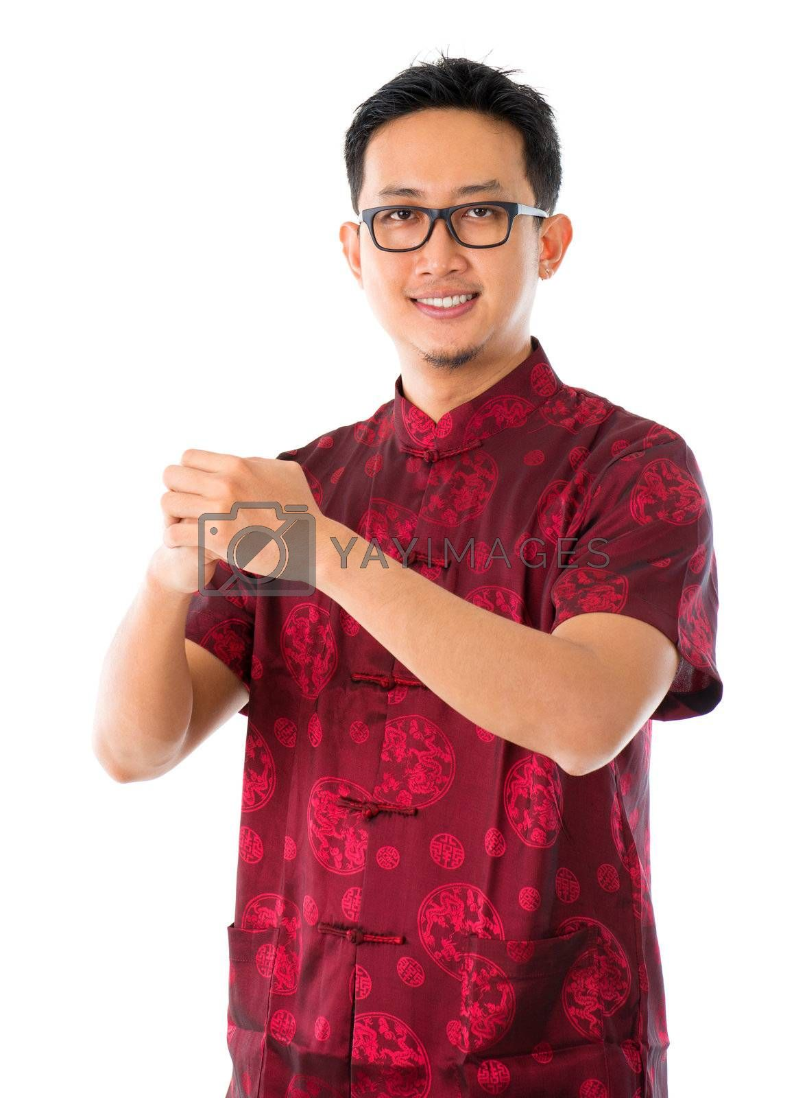 Southeast Asian Chinese man in traditional Chinese Tang suit greeting, isolated on white background