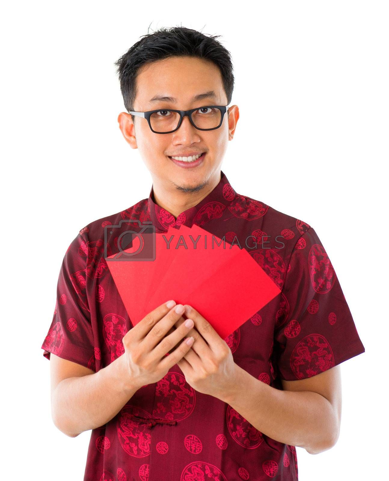 Asian Chinese man holding red packets / ang pow for happy chinese new year, isolated over white background