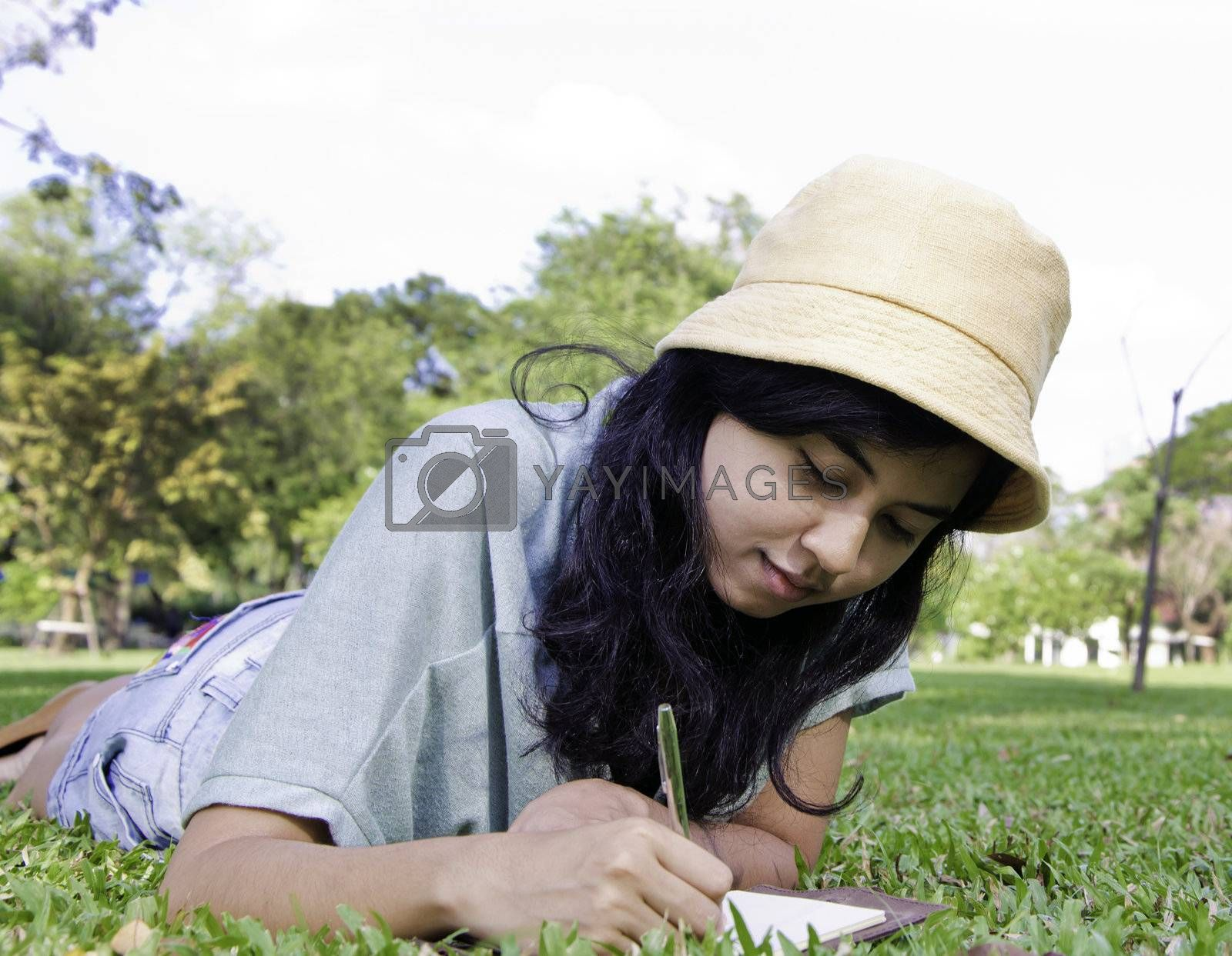 Portrait of young asia girl writting a book in park