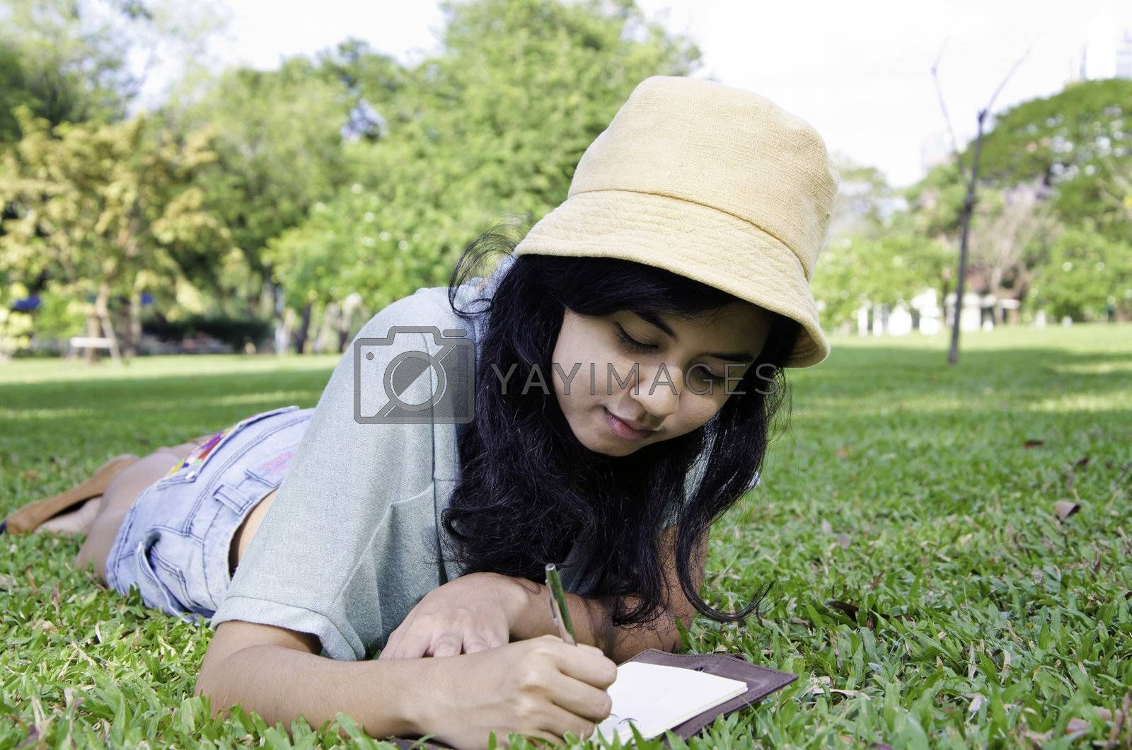 Beautiful teenage girl writting book, against green of summer park.