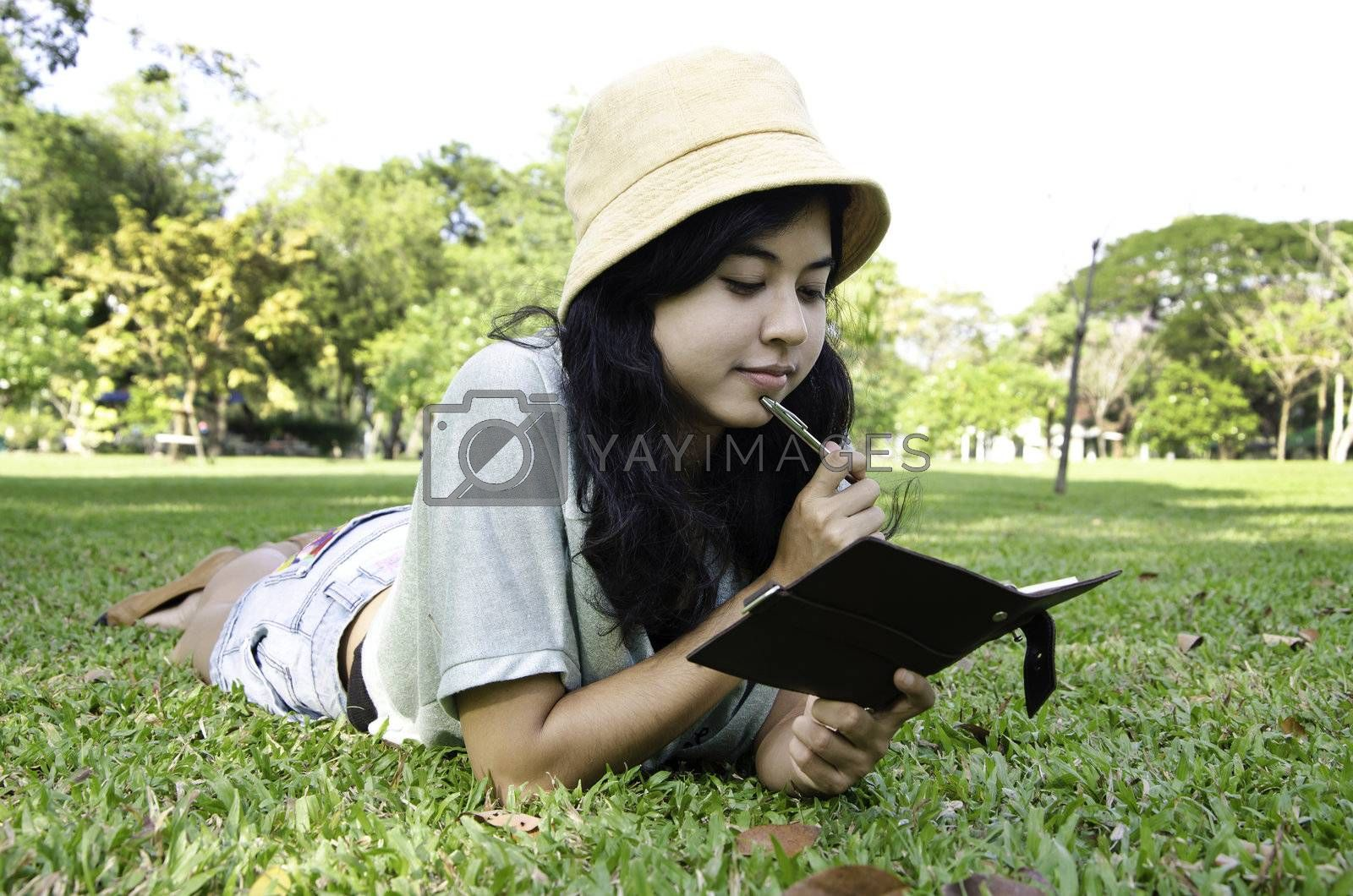 Asian woman laying on grass and thinking in park