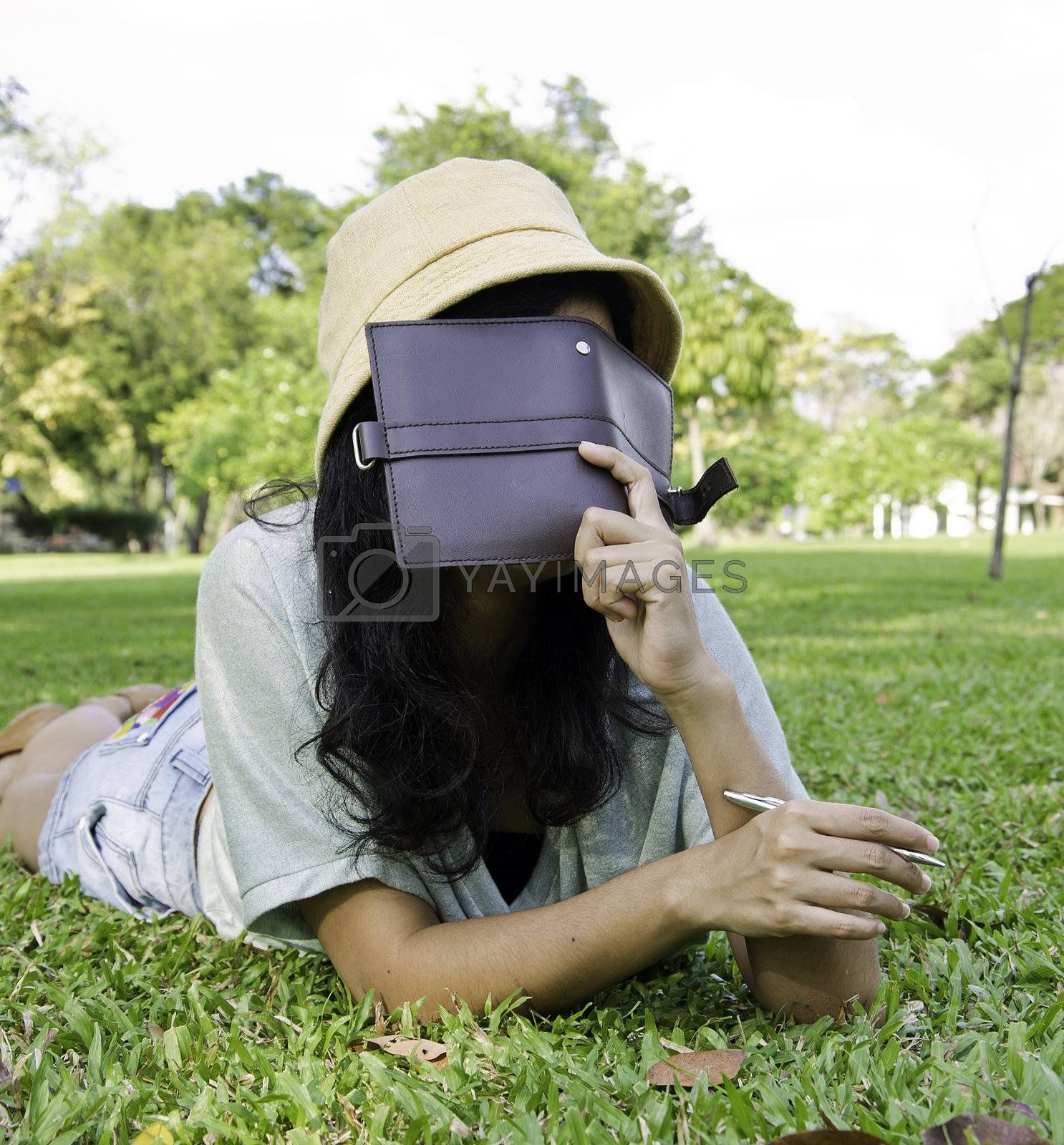 woman laying on grass and thinking in park, outdoor