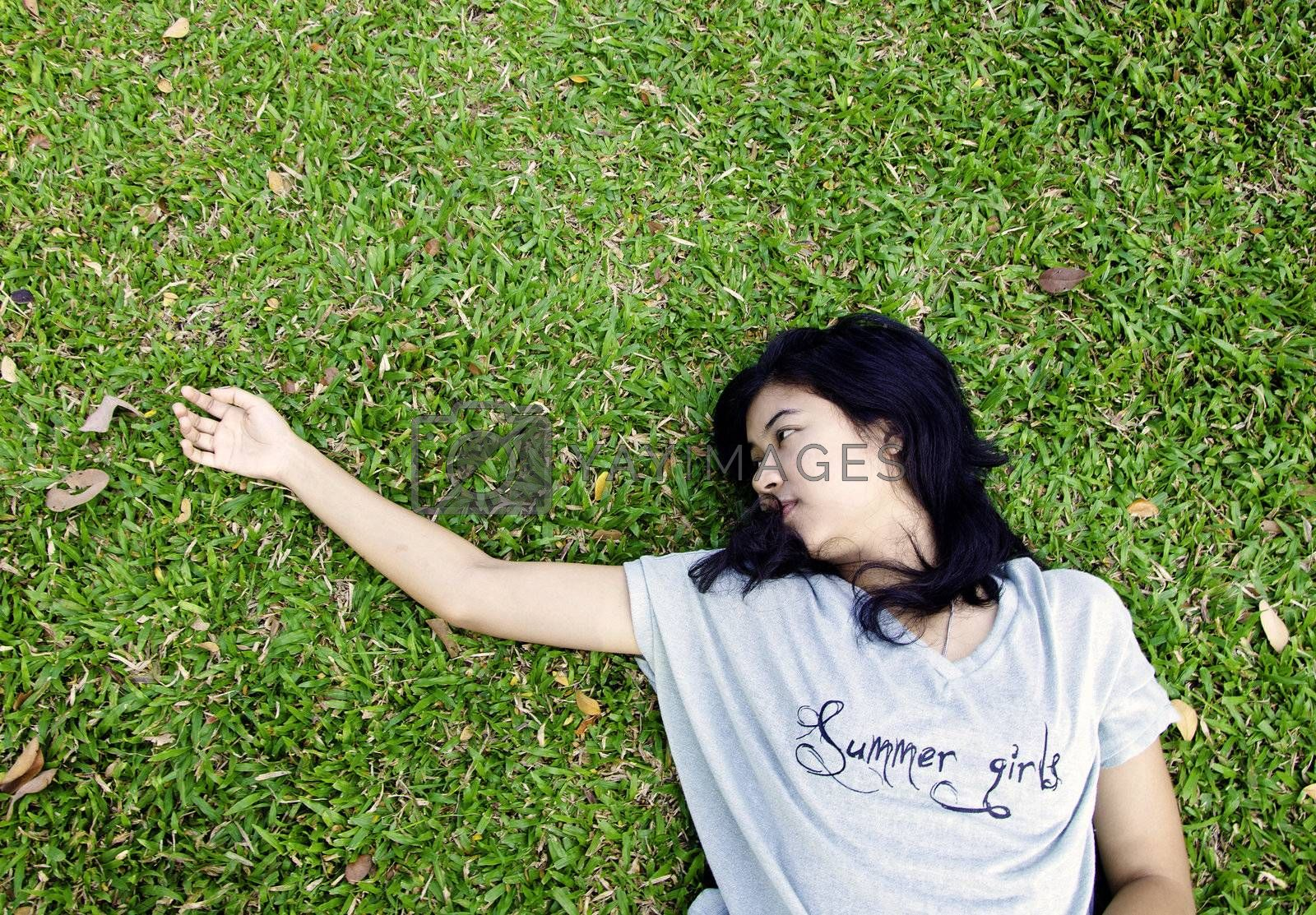 Young asian woman laying in the grass with a lot of space