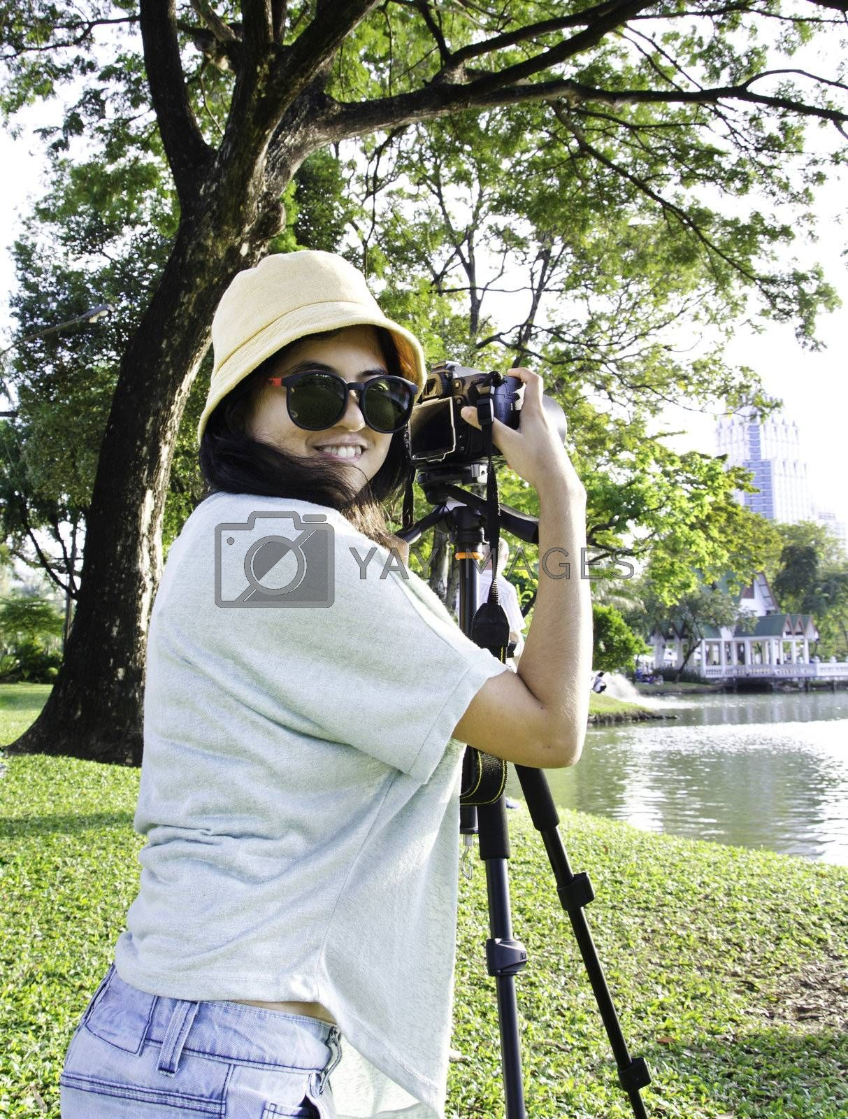 Beautiful smiling asian girl with camera on nature.
