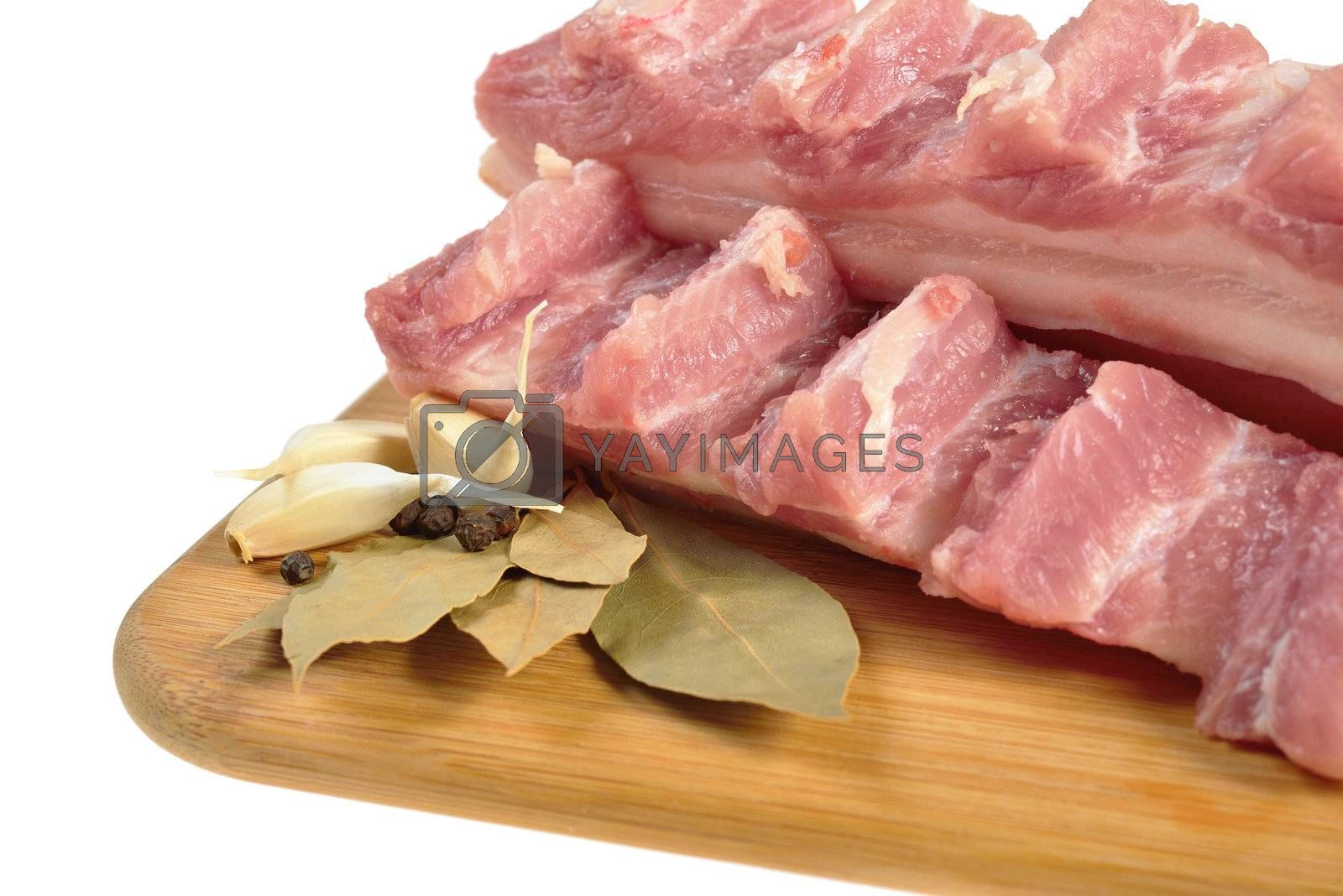 Raw bacon with ribs on a wooden cutting board. Isolated on white.
