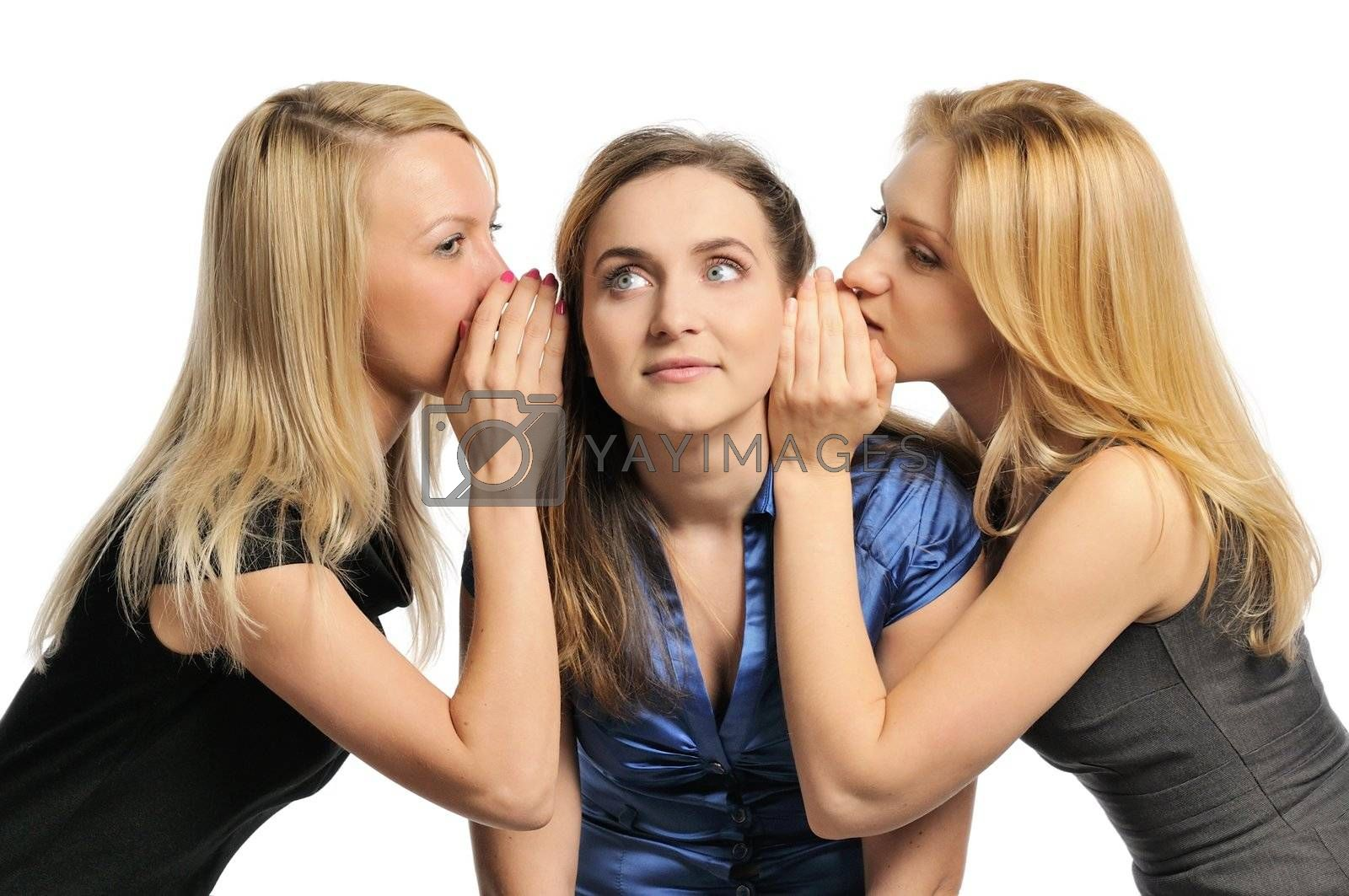Three young girls gossiping, whispering to each other's ears. Isolated on white.